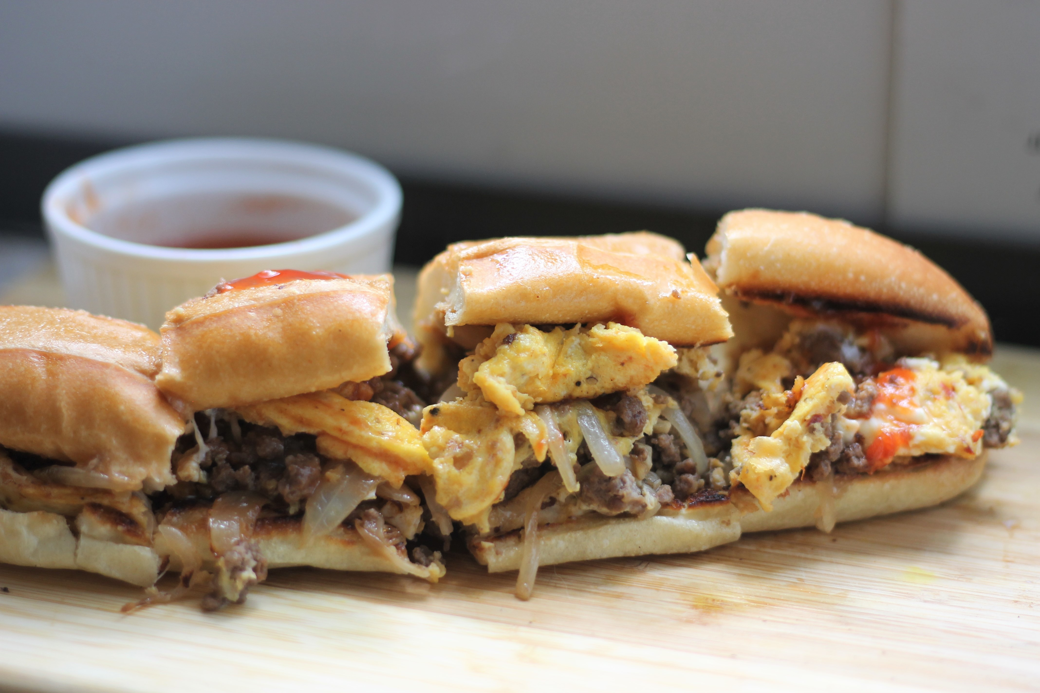A beef and egg sandwiched placed on a wooden tray