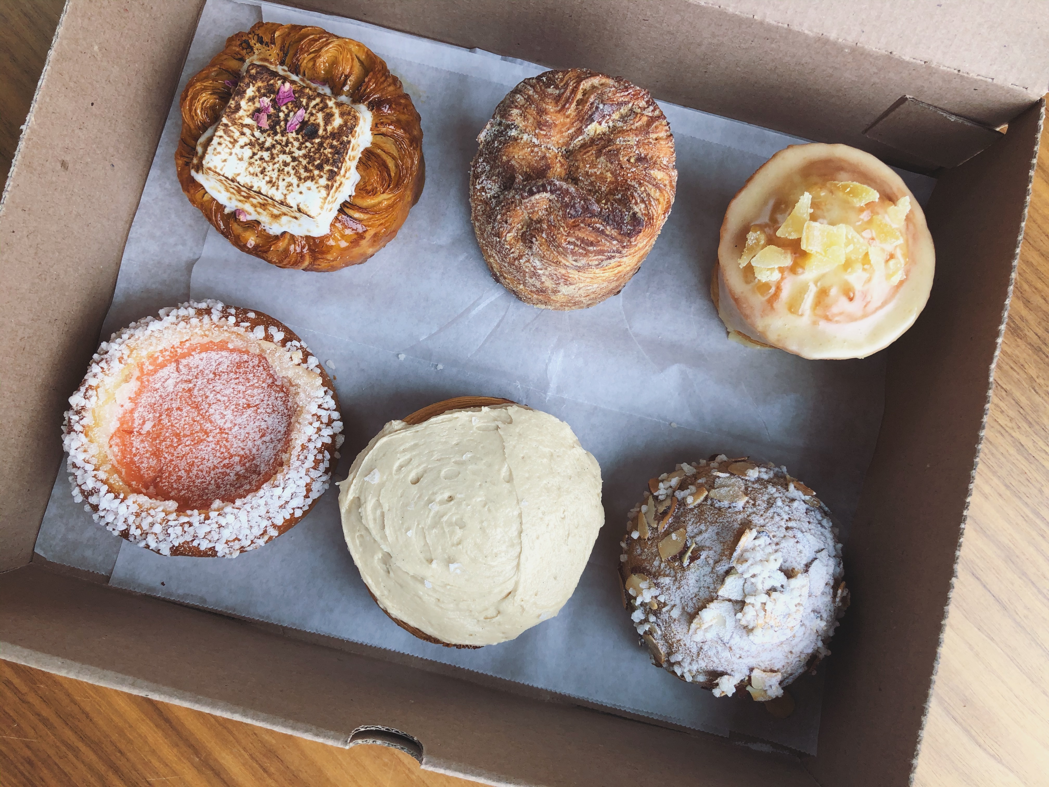 Six different pastries are lined up on wax paper in a cardboard box, including a cinnamon roll, a muffin, and more