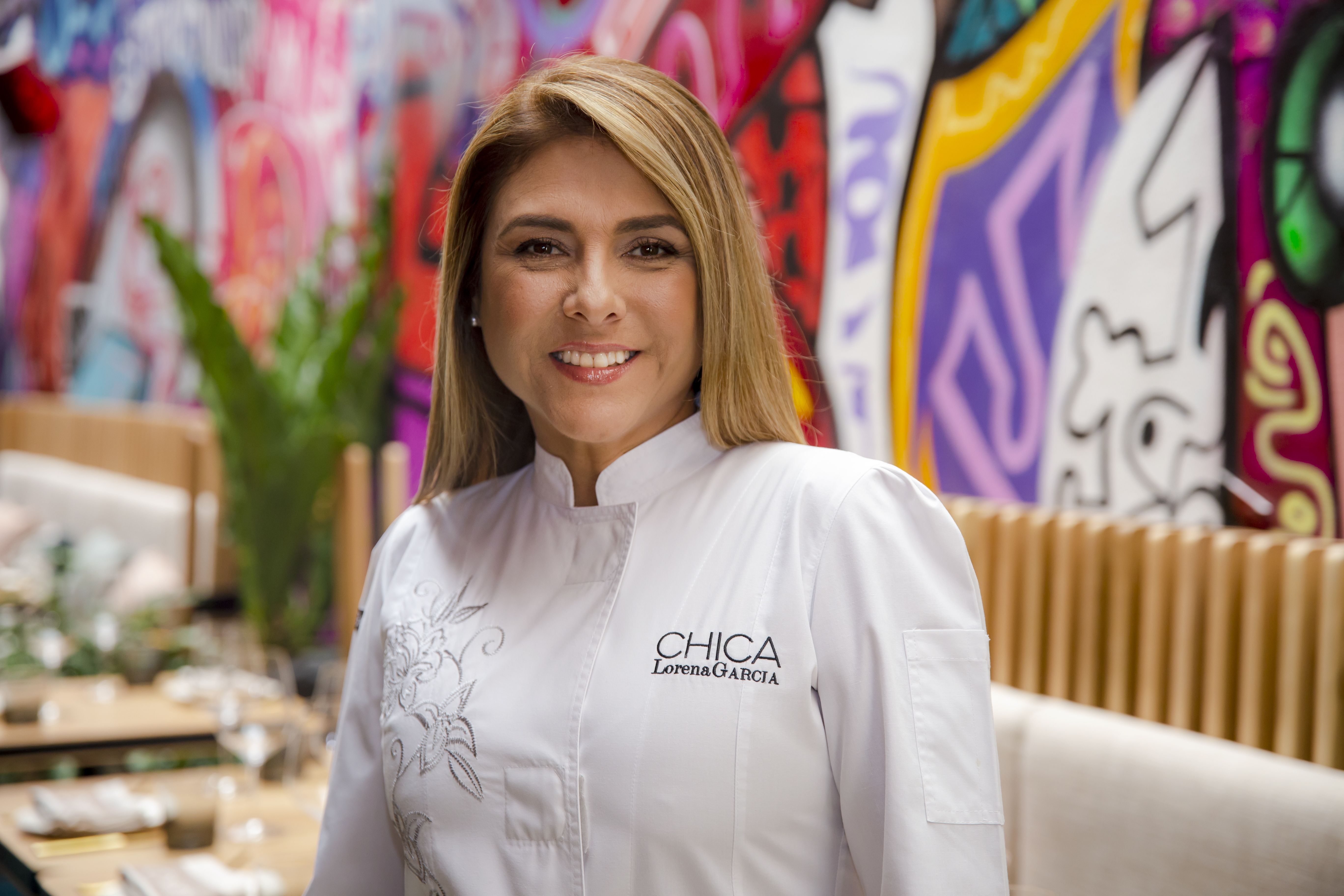 A woman wears a white chefs coat