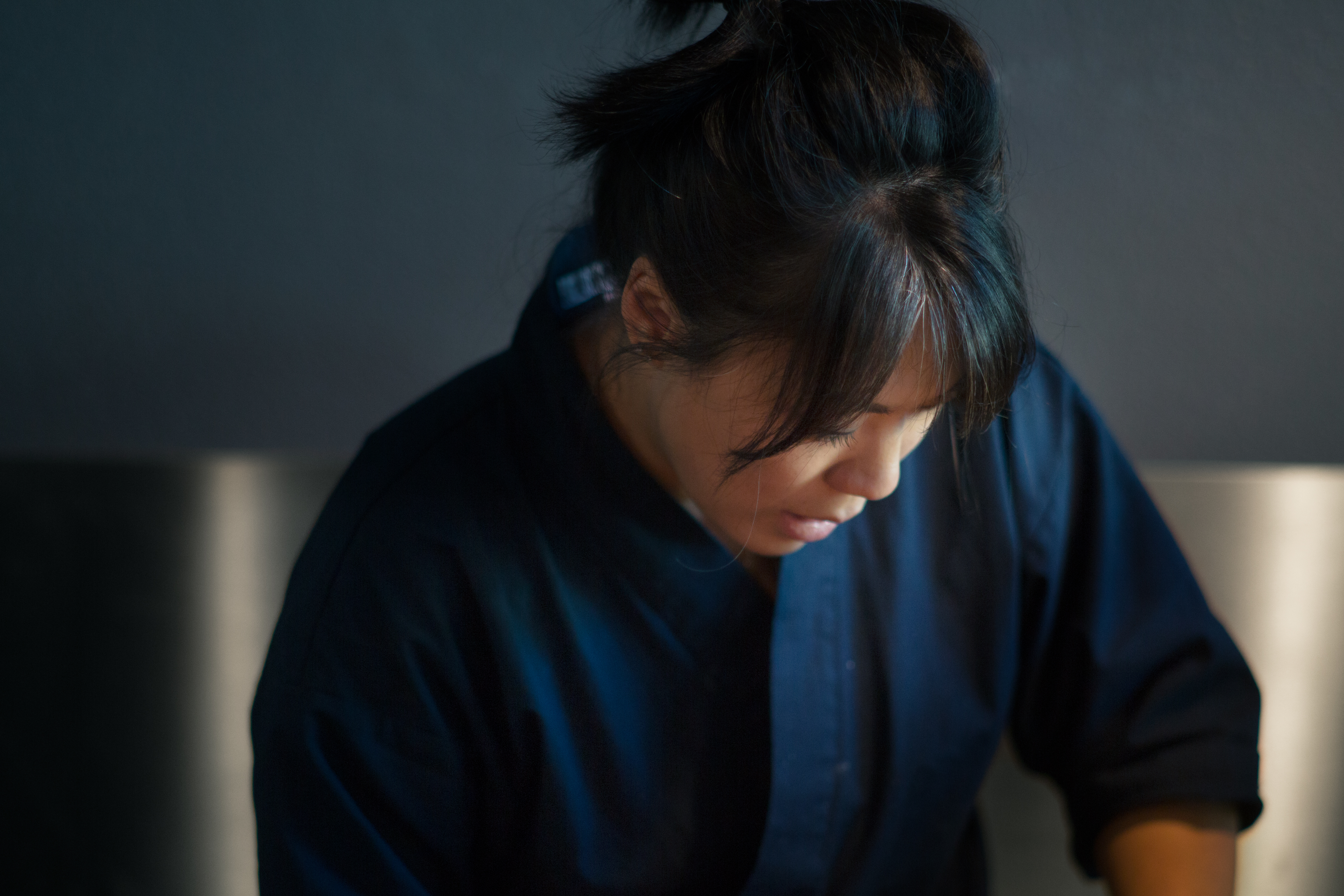 A Korean-American woman wearing a blue chef's jacket, her hair in a ponytail, scoops rice at the counter of Zilla Sake