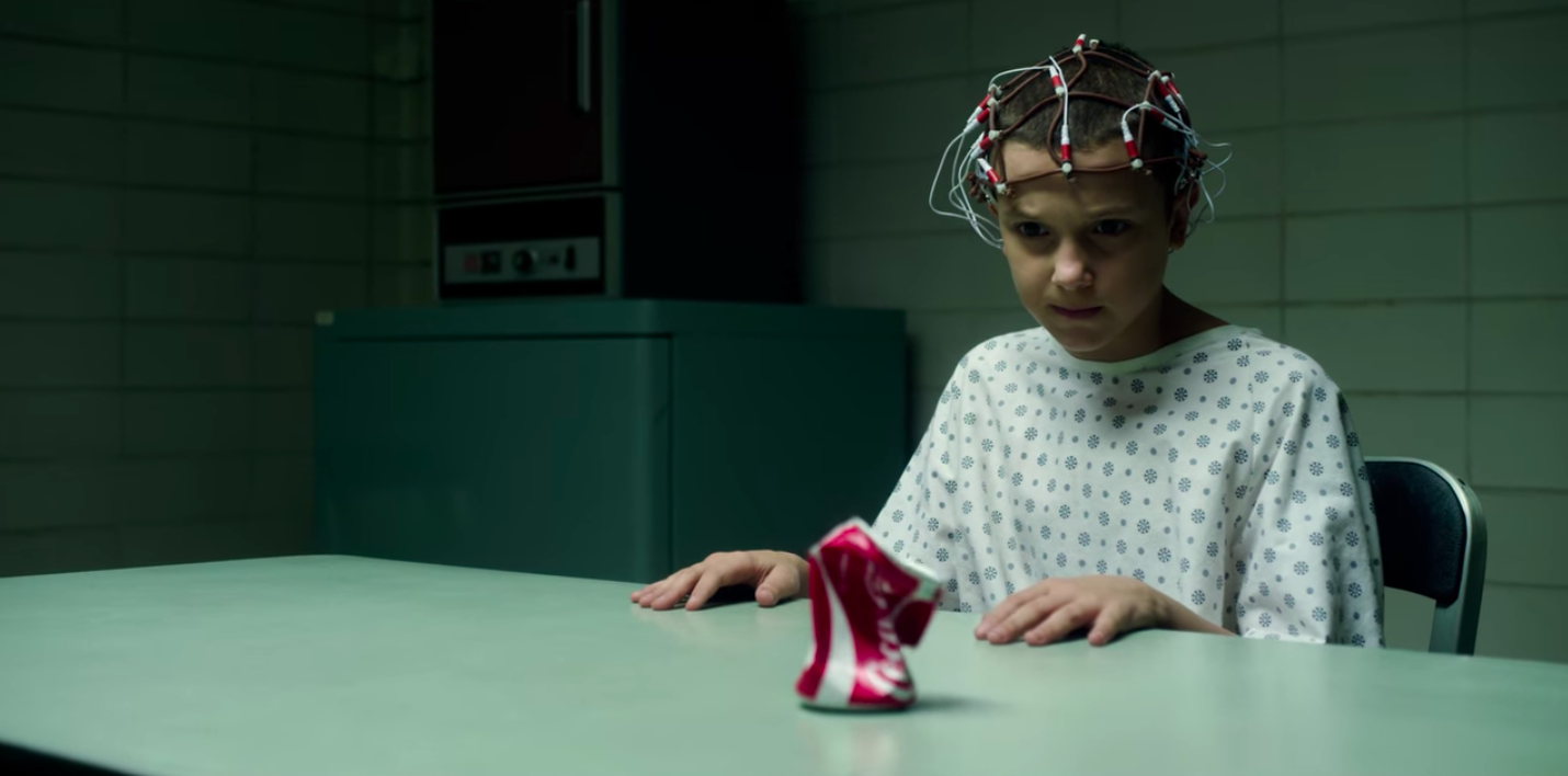 A young girl with a shaved head sits at a table in front of a crushed can of Coca-Cola.