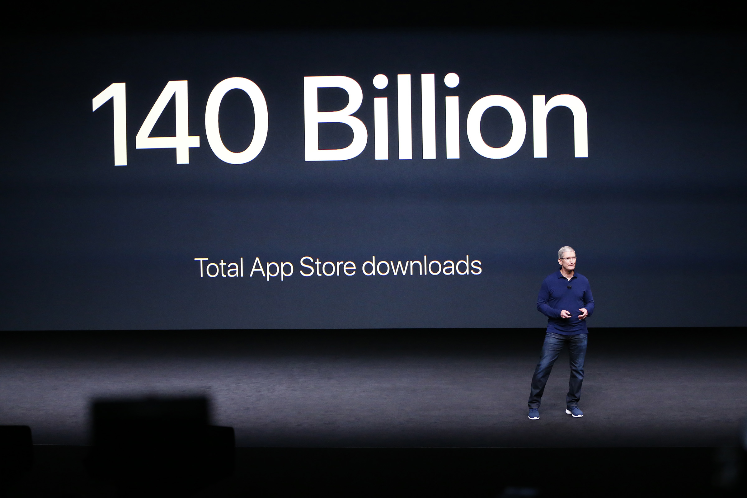 "Apple CEO Tim Cook onstage at an Apple event in front of a large screen that reads ""140 billion total app store downloads."""