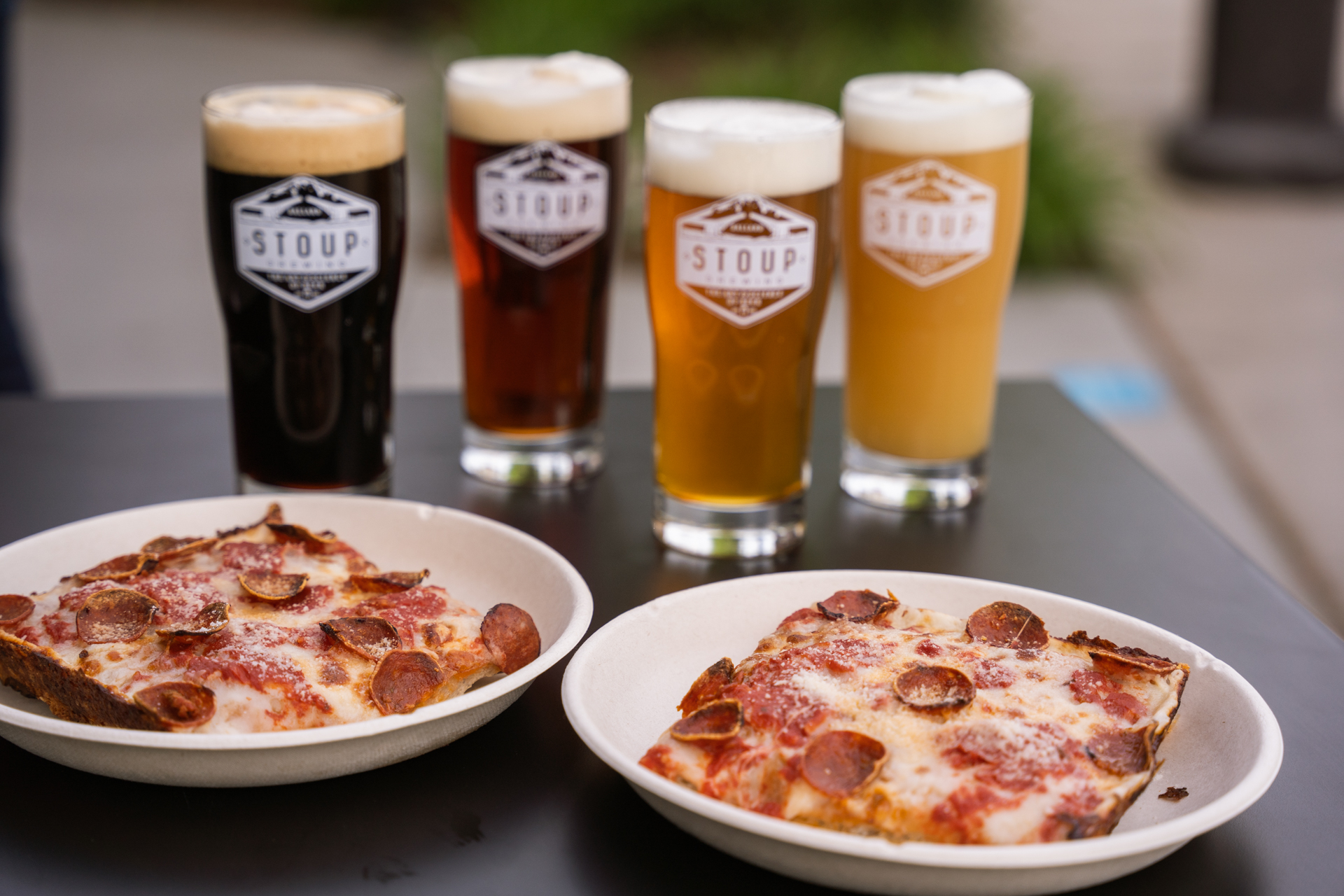 A view of four pint glasses full of beer next to two plates with square slices of pepperoni pizza