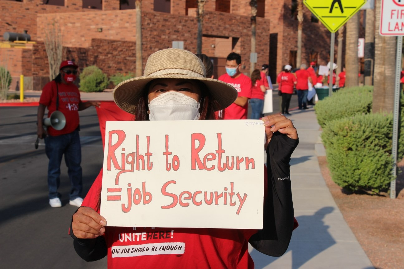 A person in a red shirt, hat and mask holds a sign that says Right to Return = Job Security outside with a line of people in red T-shirt behind