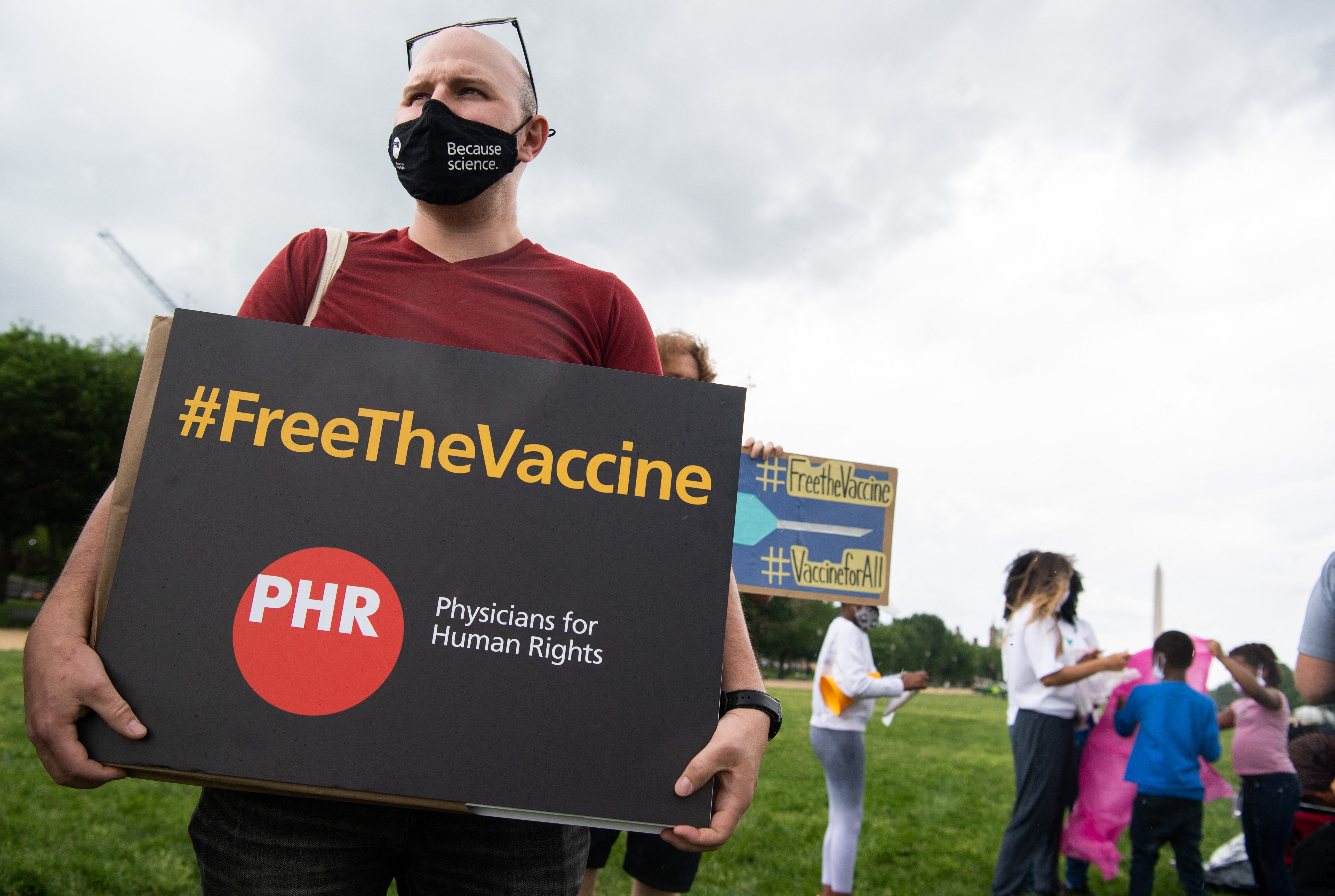 "A demonstrator holds a placard that reads ""free the vaccine, PHR physicians for human rights."""