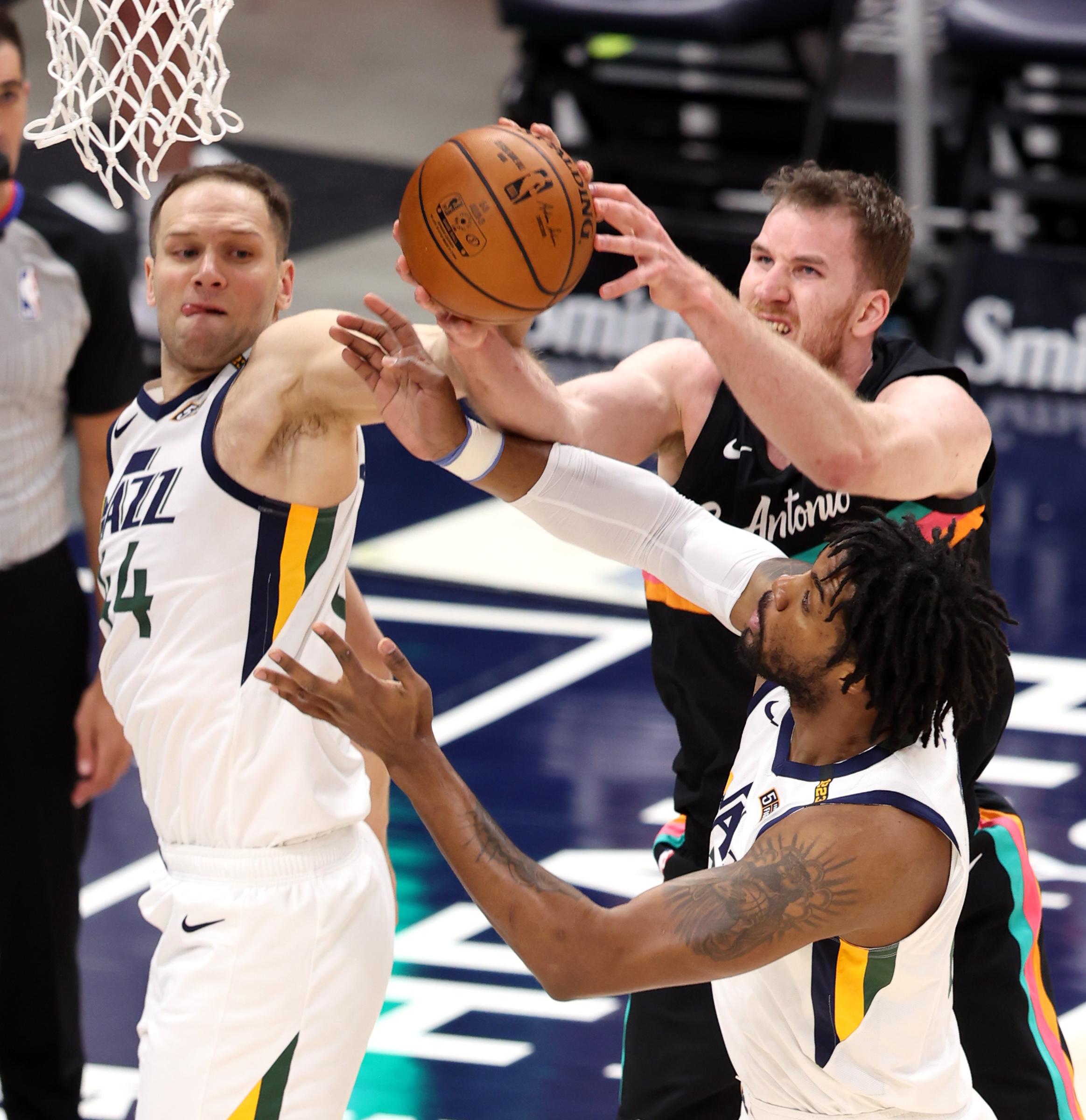 Utah Jazz forward Bojan Bogdanovic (44) and Utah Jazz center Derrick Favors (15) battle San Antonio Spurs center Jakob Poeltl (25) for the ball as the Utah Jazz and the San Antonio Spurs play an NBA basketball game at Vivint Arena in Salt Lake City on Wednesday, May 5, 2021.