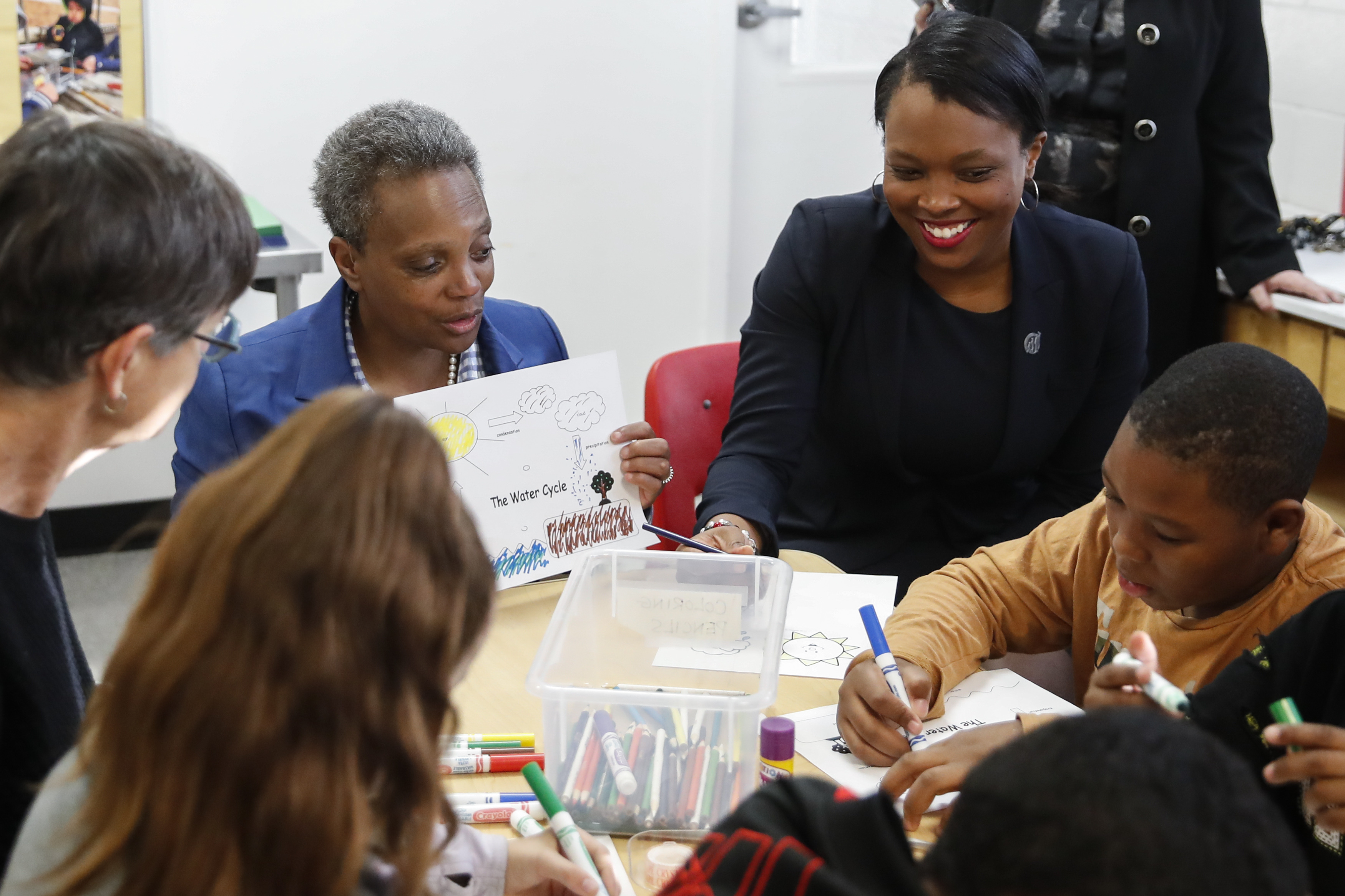 Janice Jackson sits next to Mayor Lori Lightfoot at a table with students.