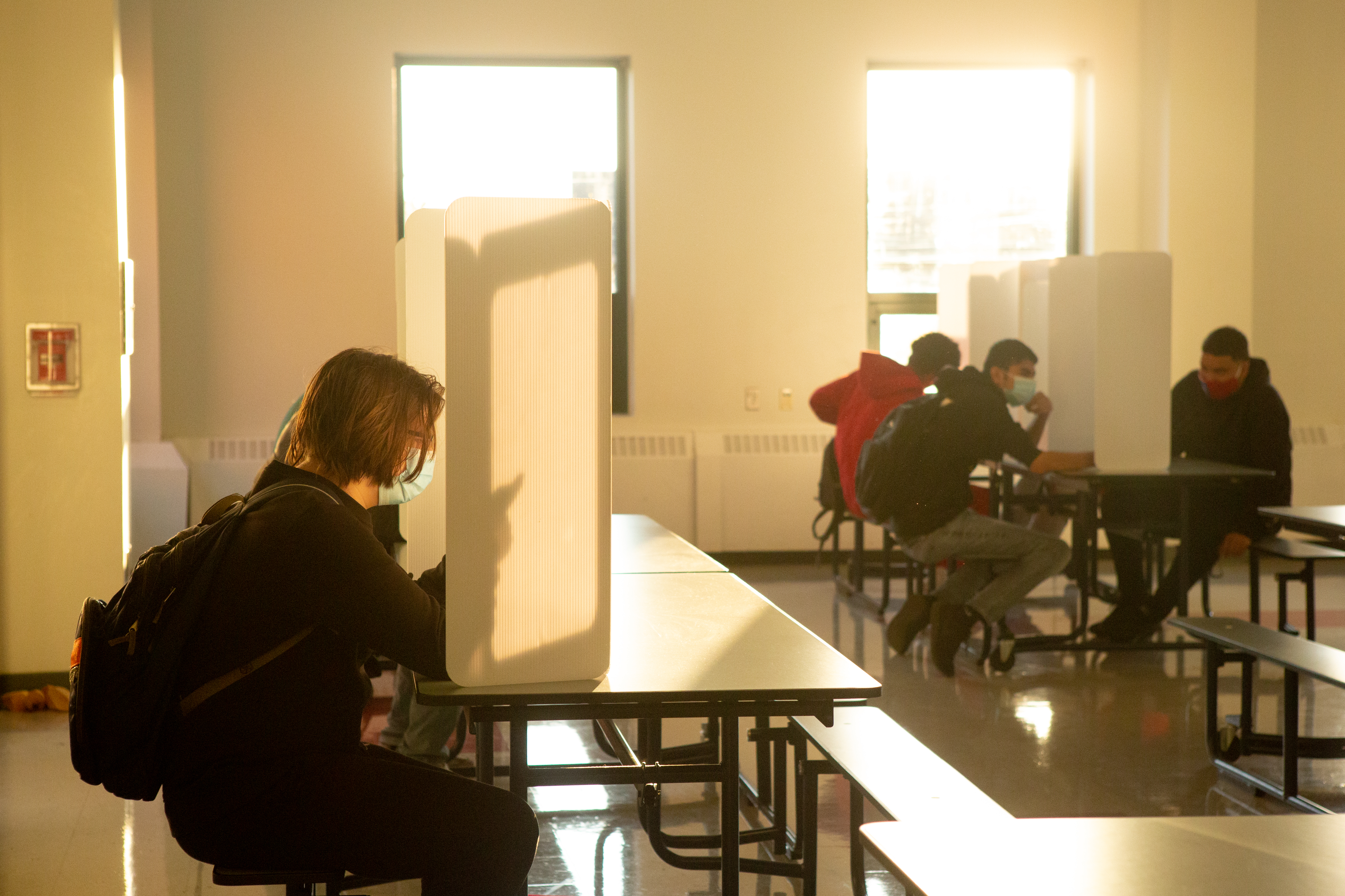 A student wearing a backpack sits on a bench at a table with a trifold partition on top, while three male students in the background also sit at table with partitions.
