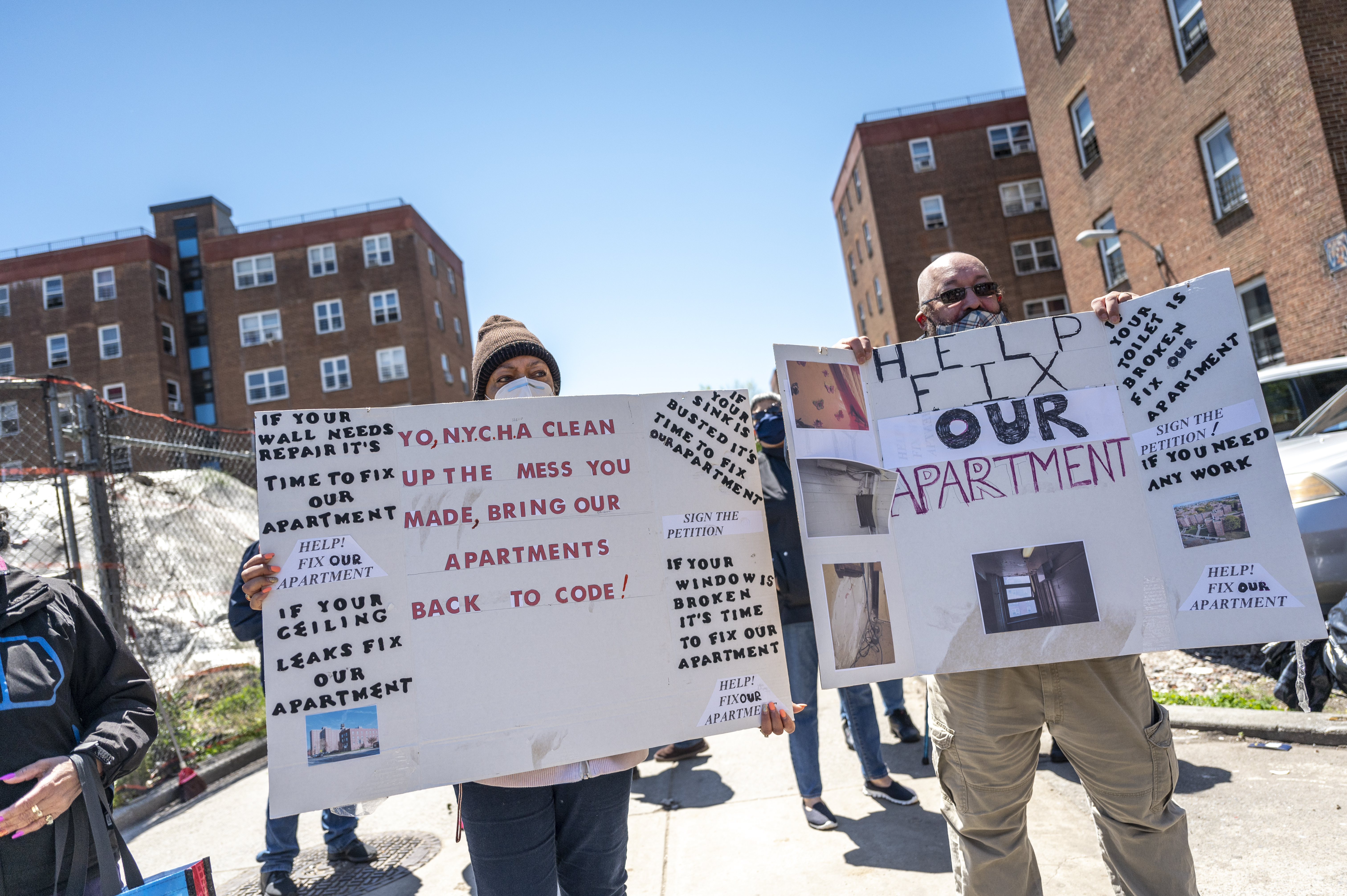Protestors hold up signs with pictures showing damage to apartments at the Red Hook Houses, May 6, 2021.