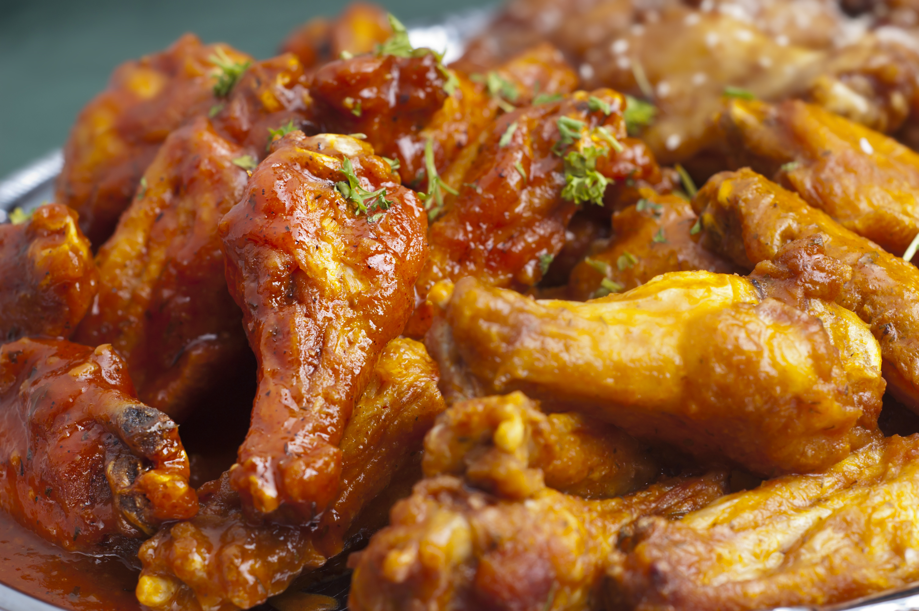 chicken wings, up close, covered in buffalo sauce.