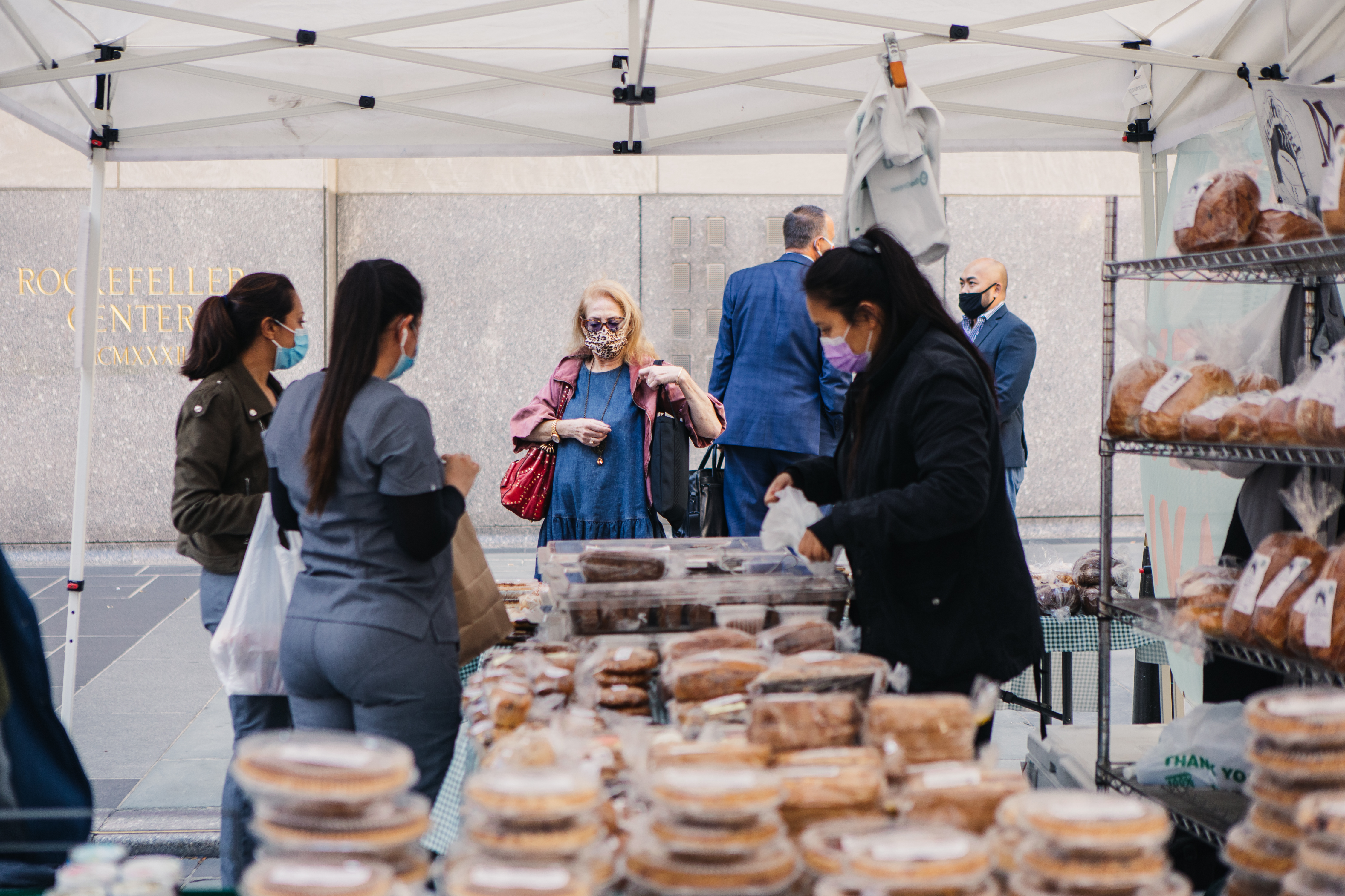 Customers gather around a tented vendor at a lunchtime market at the Rockefeller Center in Manhattan, New York
