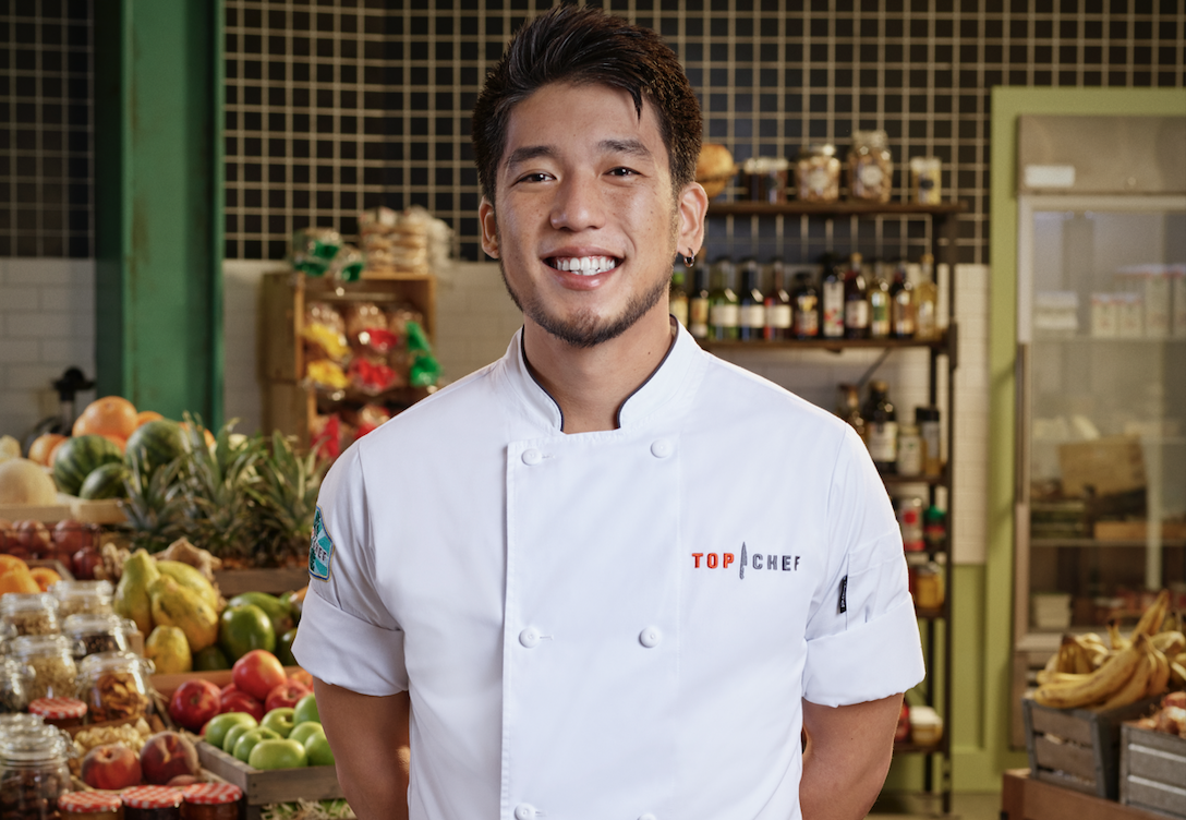 "A photo of Shota Nakajima in a ""Top Chef"" apron with shelves of pantry items in the background"