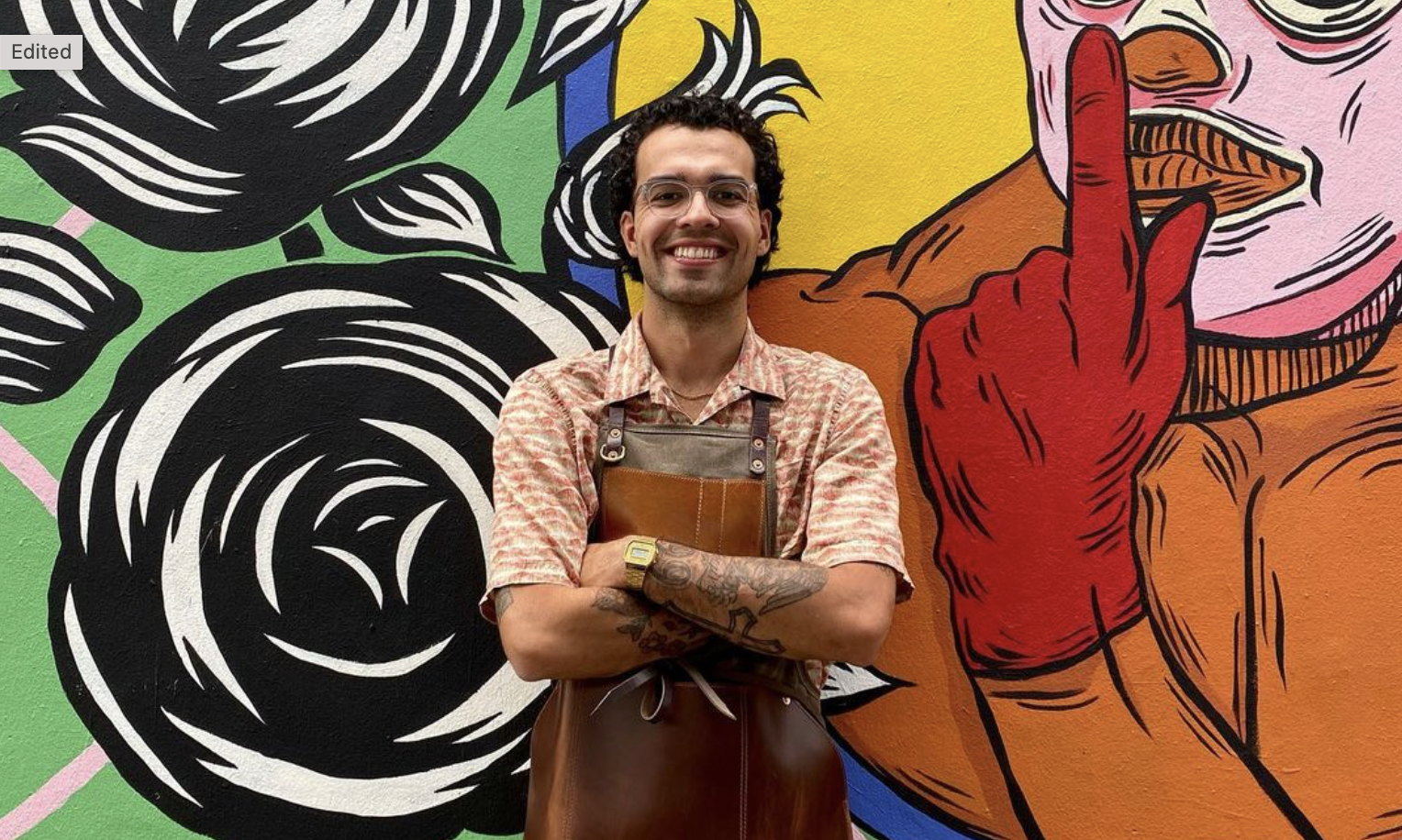 A man with glasses and an apron smiles in front of a mural of a luchador