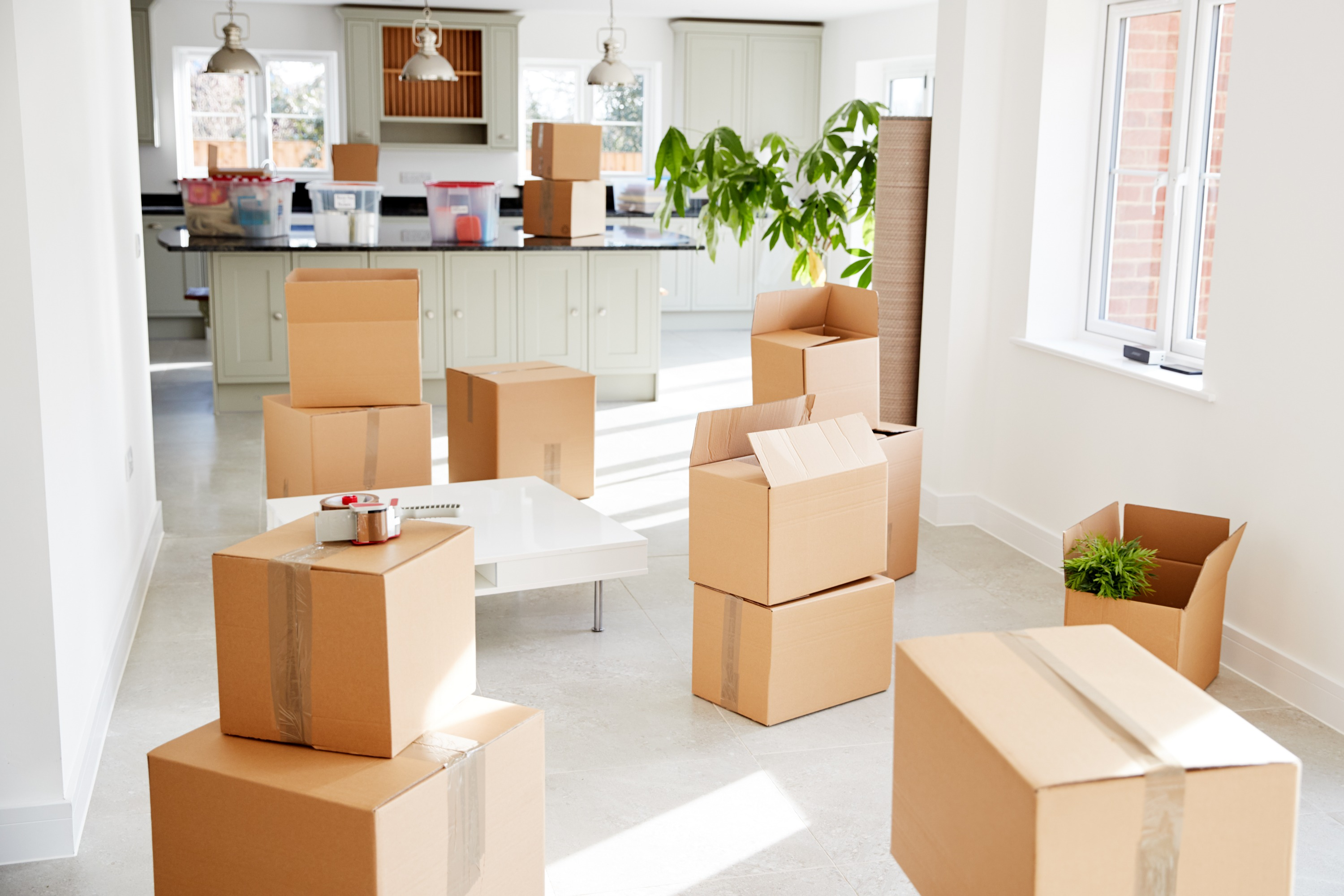 Moving boxes near a kitchen of a home with white walls, white floor, and bright windows.