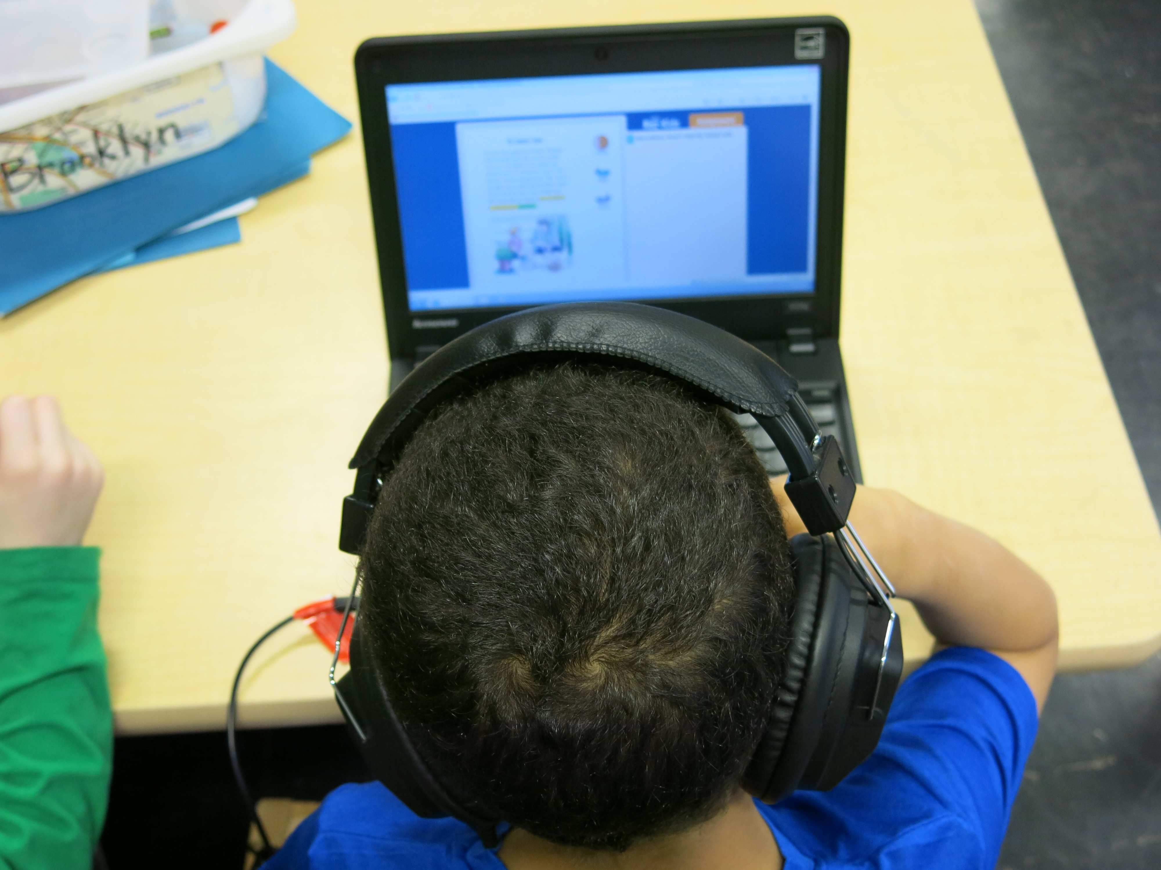 A young student wearing headphones and working on a laptop.