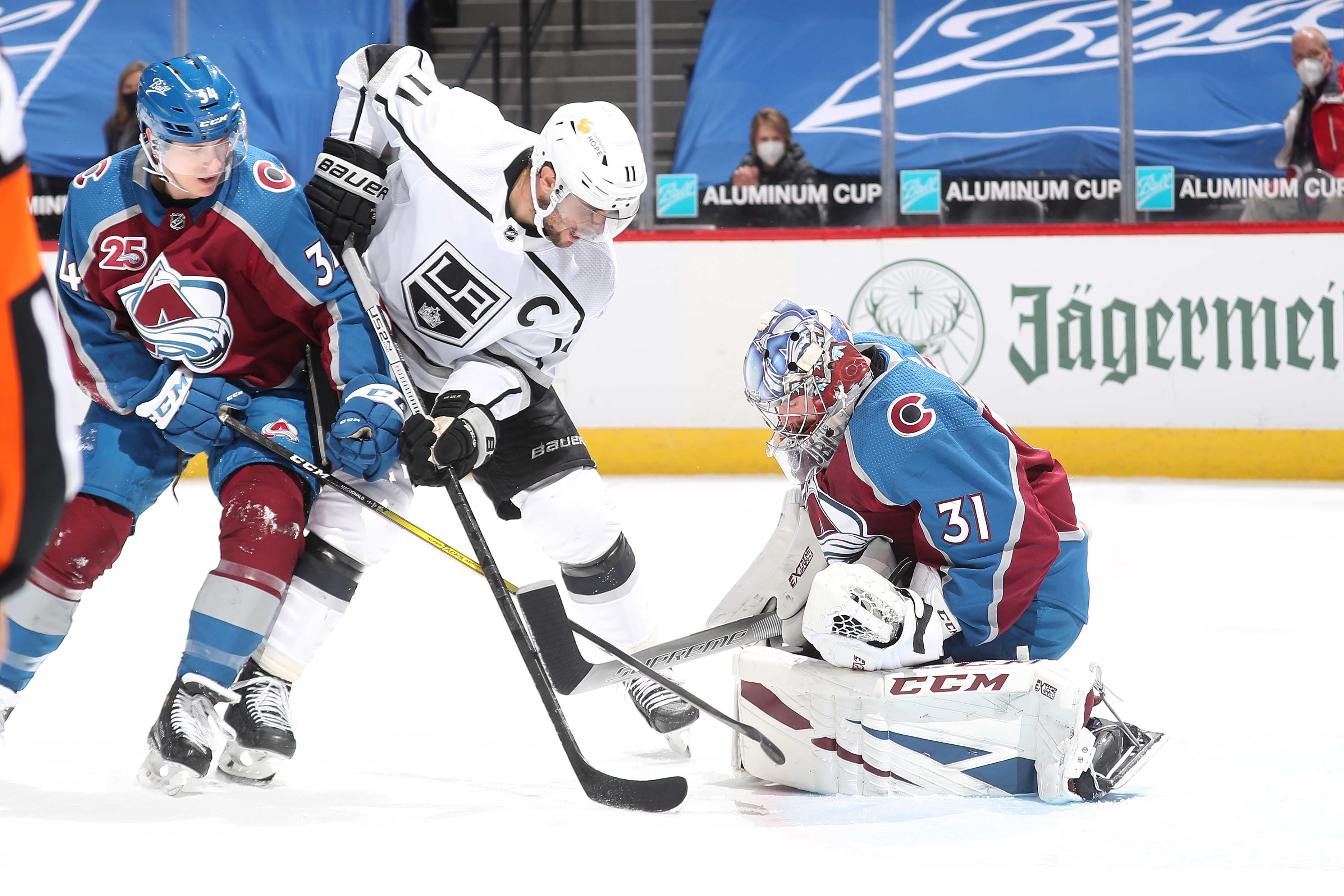 Goaltender Philipp Grubauer #31 of the Colorado Avalanche looks to make a save against Anze Kopitar #11 of the Los Angeles Kings next to teammate Jacob MacDonald #34 at Ball Arena on March 14, 2021 in Denver, Colorado. The Avalanche defeated the Kings 4-1.