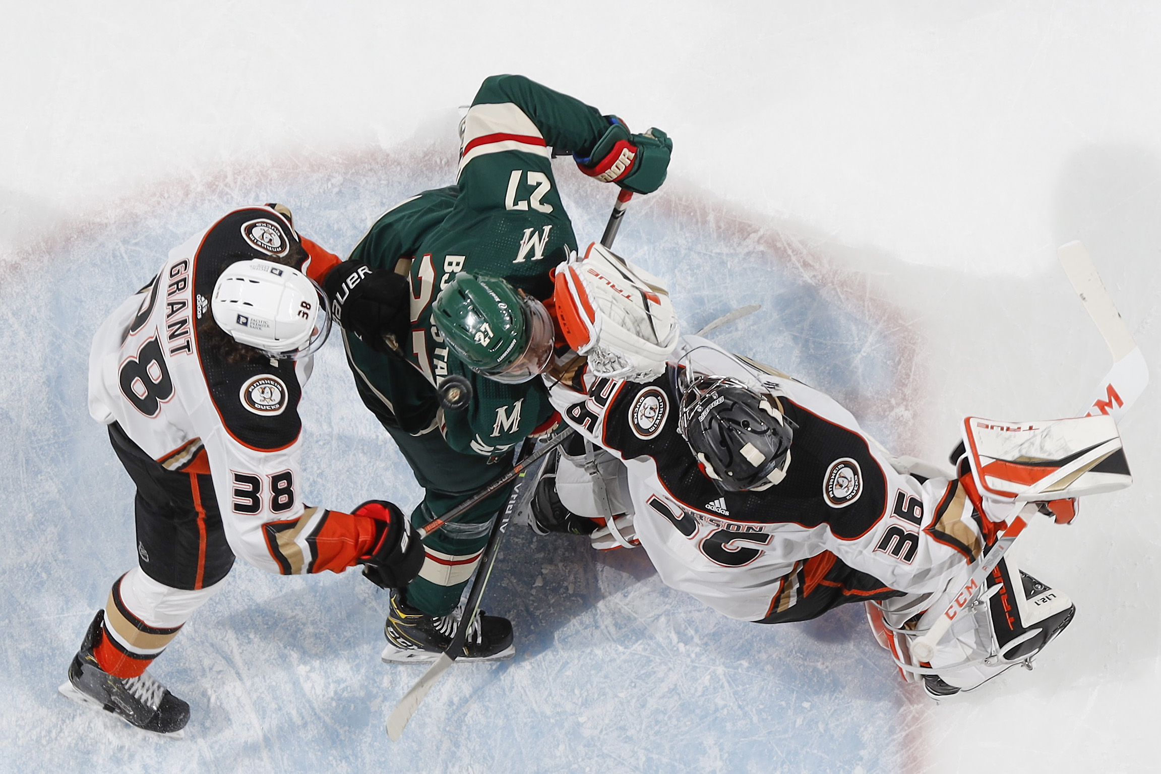 Derek Grant #38 and John Gibson #36 of the Anaheim Ducks defend against Nick Bjugstad #27 of the Minnesota Wild during the game at the Xcel Energy Center on May 7, 2021 in Saint Paul, Minnesota.