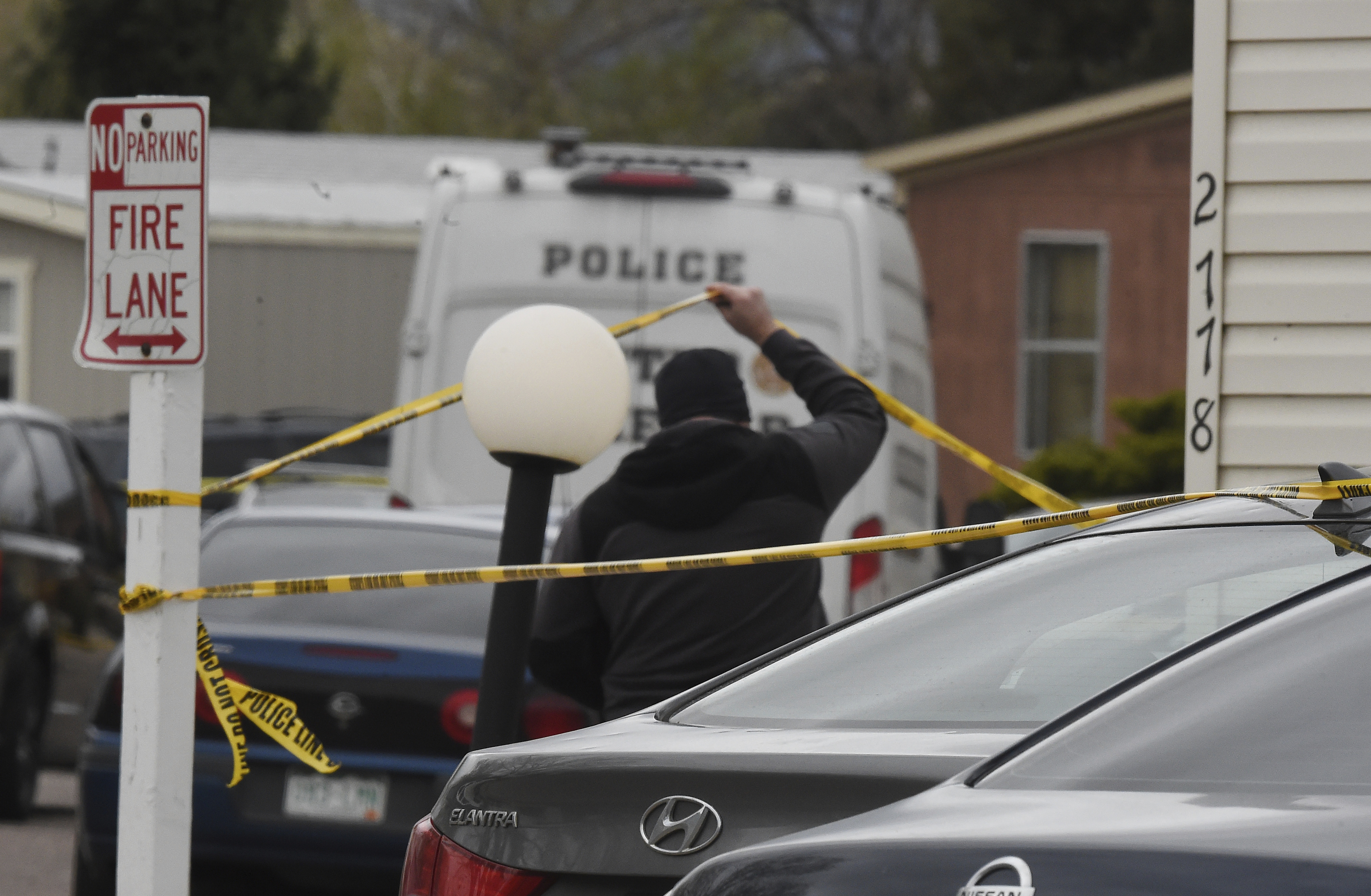A Colorado Springs Police Department officer lifts up crime tape at the scene where multiple people were shot and killed early Sunday in Colorado Springs, Colo.