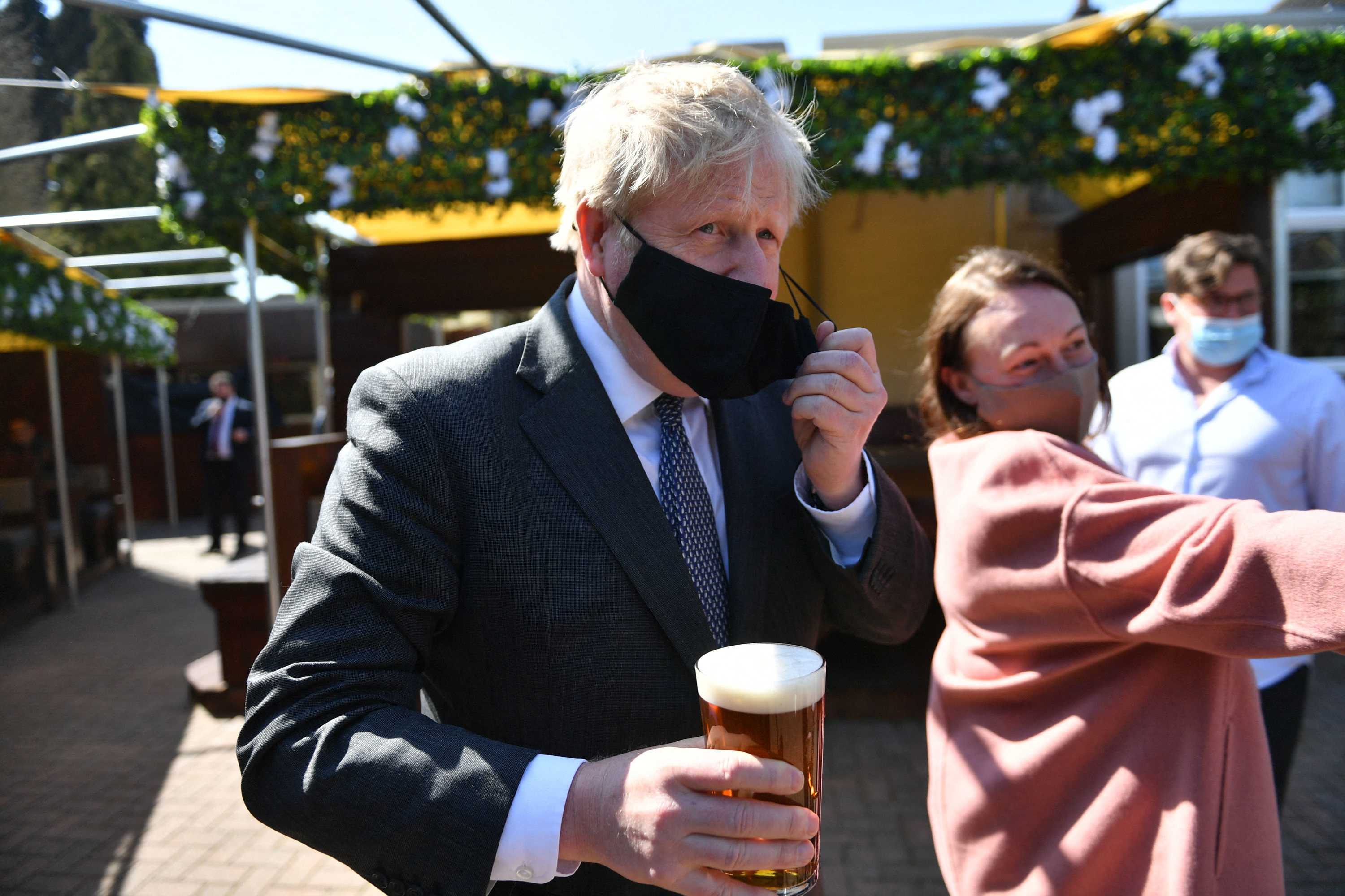 Boris Johnson removes his mask while carrying a pint in a pub garden, neither of which are allowed under current coronavirus rules