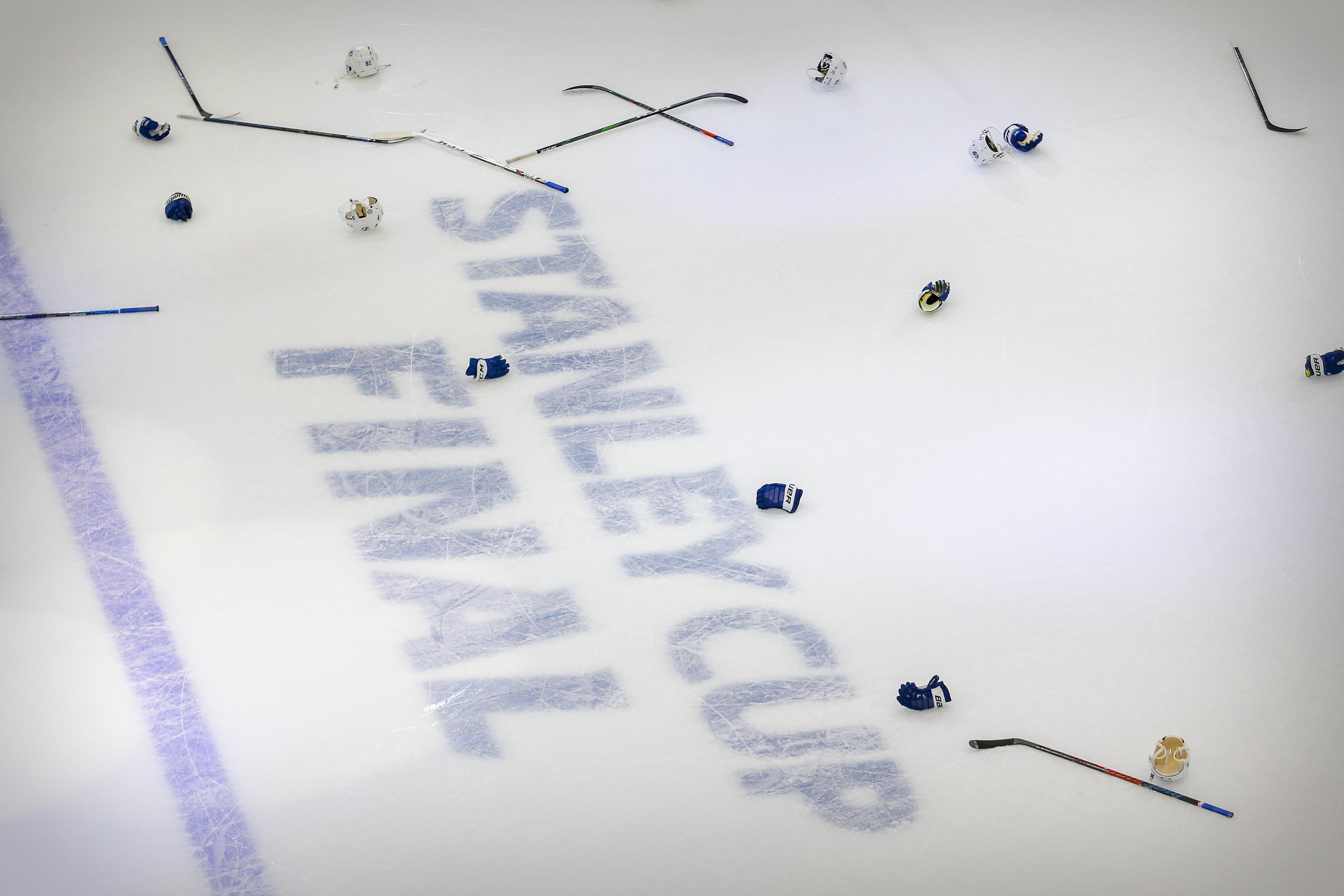 在罗杰斯广场举行的2020年斯坦利杯决赛第六场比赛中,坦帕湾闪电队击败达拉斯星队后,冰上和斯坦利杯决赛的标志和球员的棒子和手套。