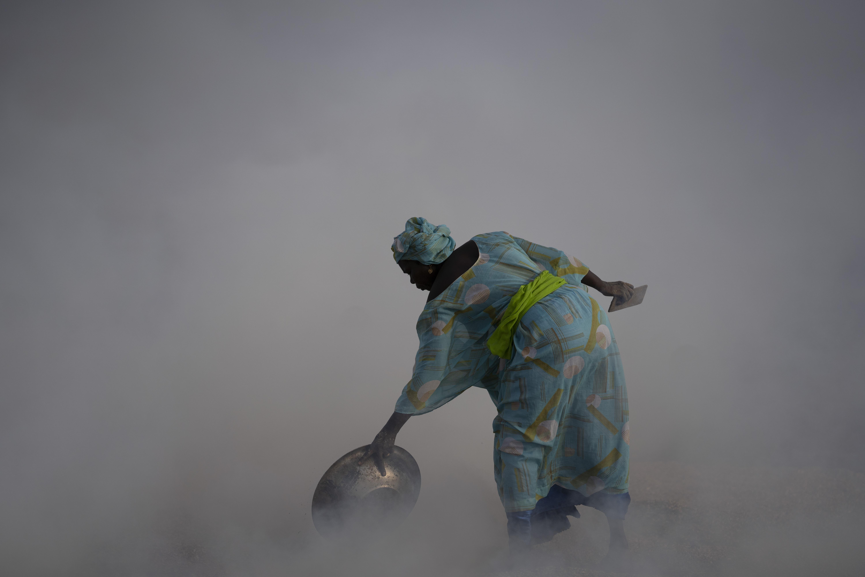 Ndeye Yacine Dieng drops embers over peanut shells covering fish as she walks amidst the smoke on Bargny beach, some 22 miles east of Dakar, Senegal, Wednesday April 21, 2021.