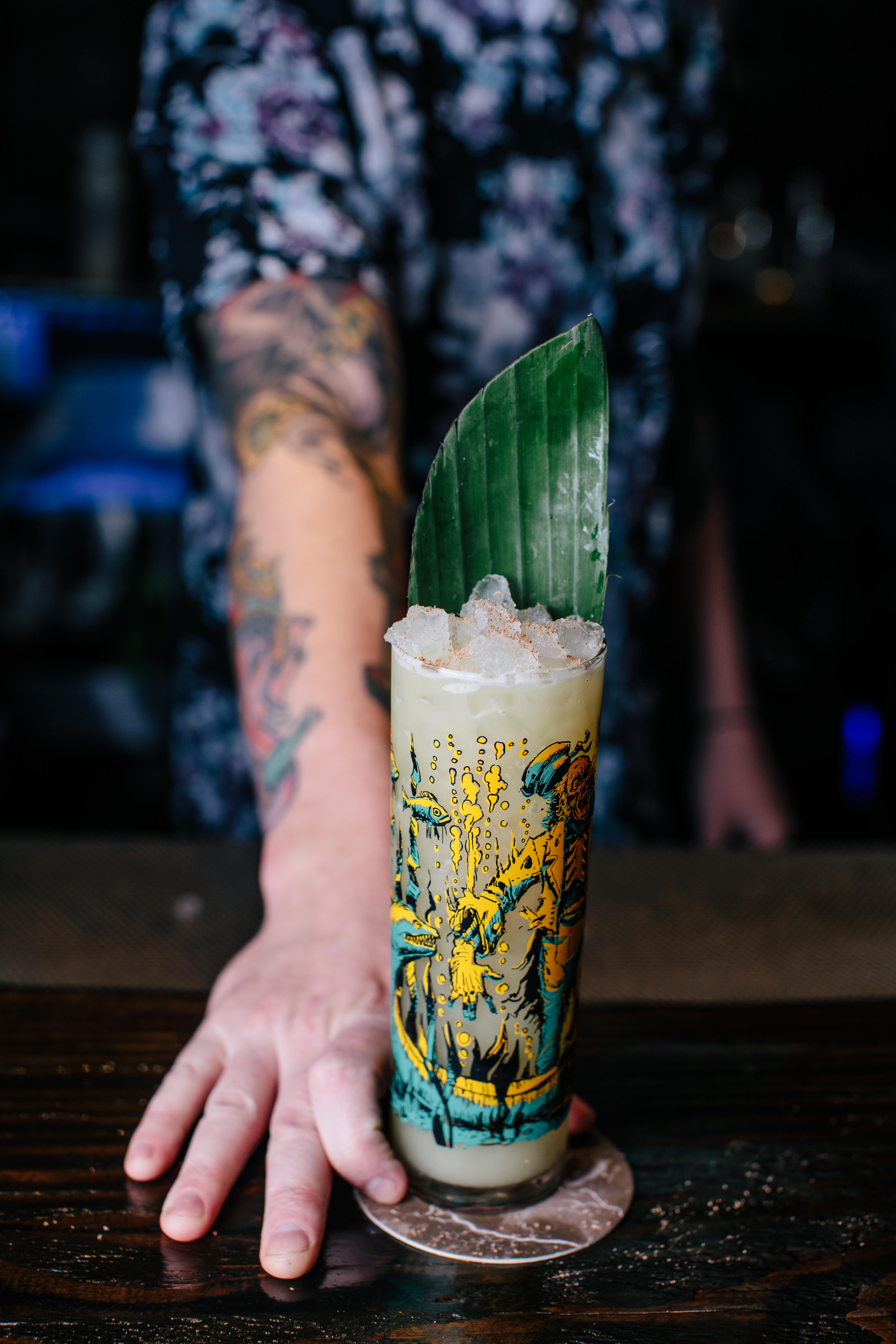 白色纹身的侍酒者推动一个朝向相机的大绿叶的Tiki鸡尾酒。