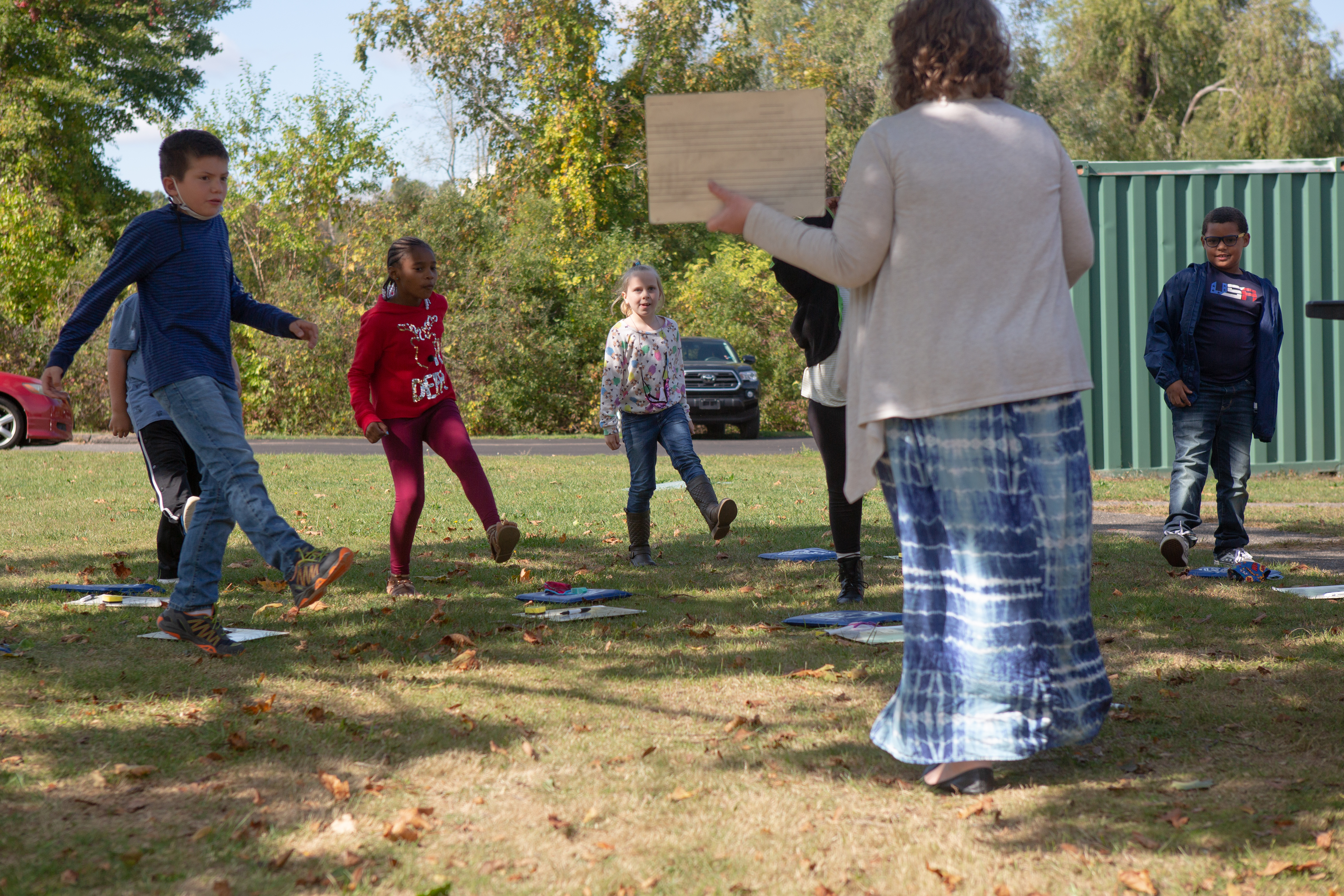 A teacher in a white sweater and a long blue-and-white skirt stand on a lawn facing about a half-dozen standing students who are each lifting one leg together.