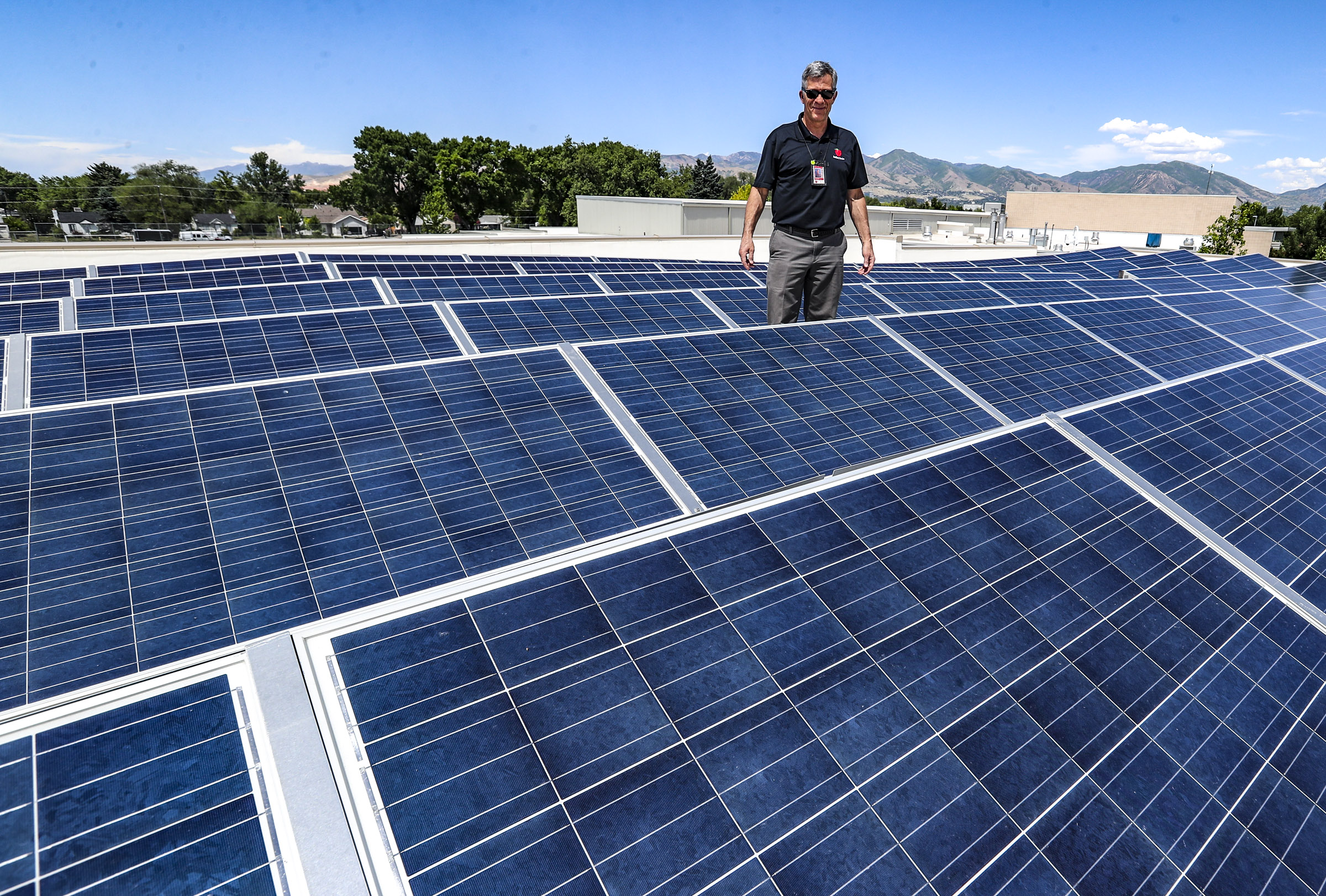 Greg Libecci, energy and resource manager for the Salt Lake City School District, stands with solar panels on the roof of Mountain View Elementary School in Salt Lake City on Wednesday, June 3, 2020.
