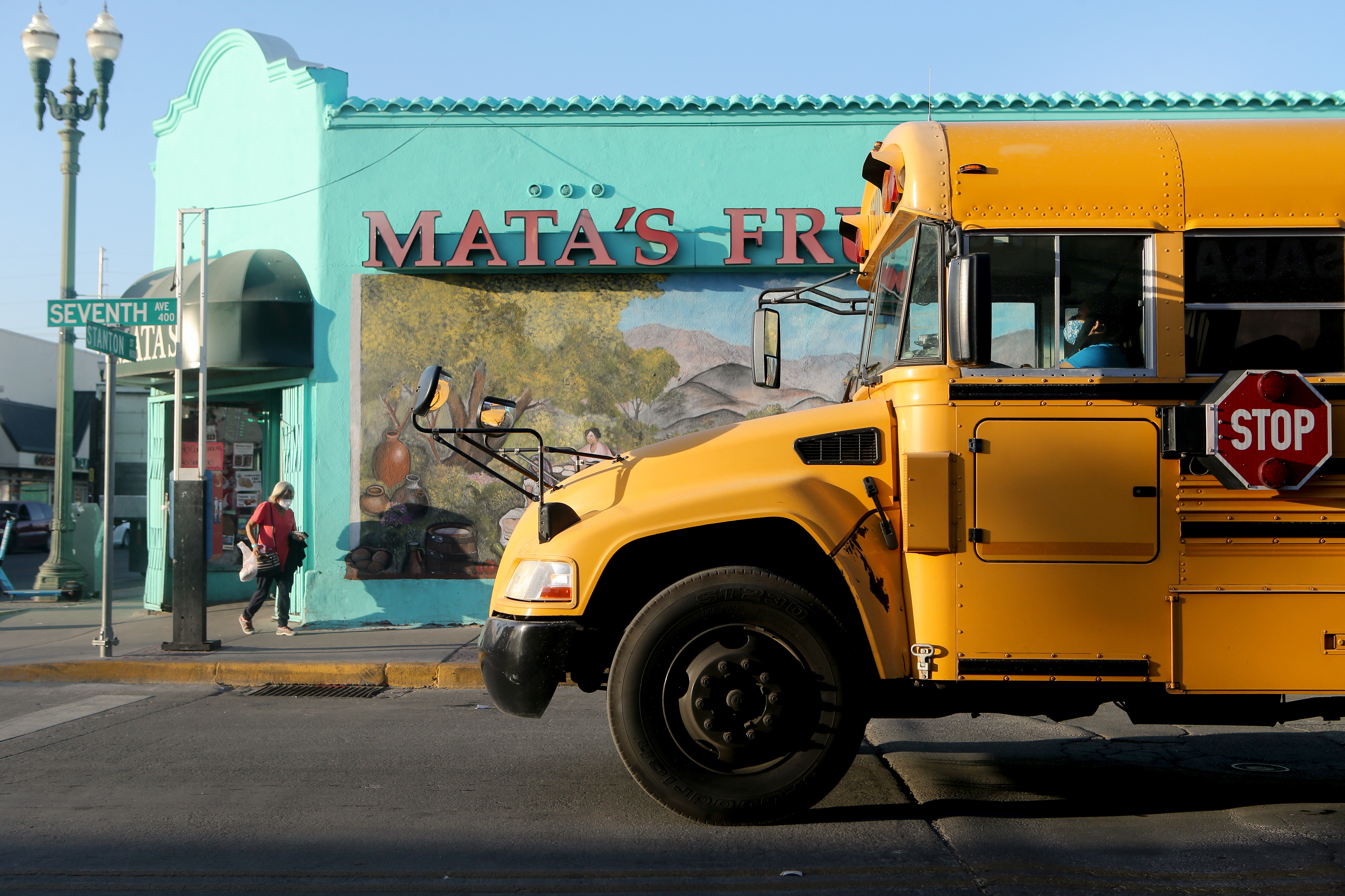 A yellow school bus with a masked driver drives up to an intersection in El Paso, Tex. There is a vibrant teal-colored storefront with a blonde woman wearing a pink shirt walking by on the corner of the street.