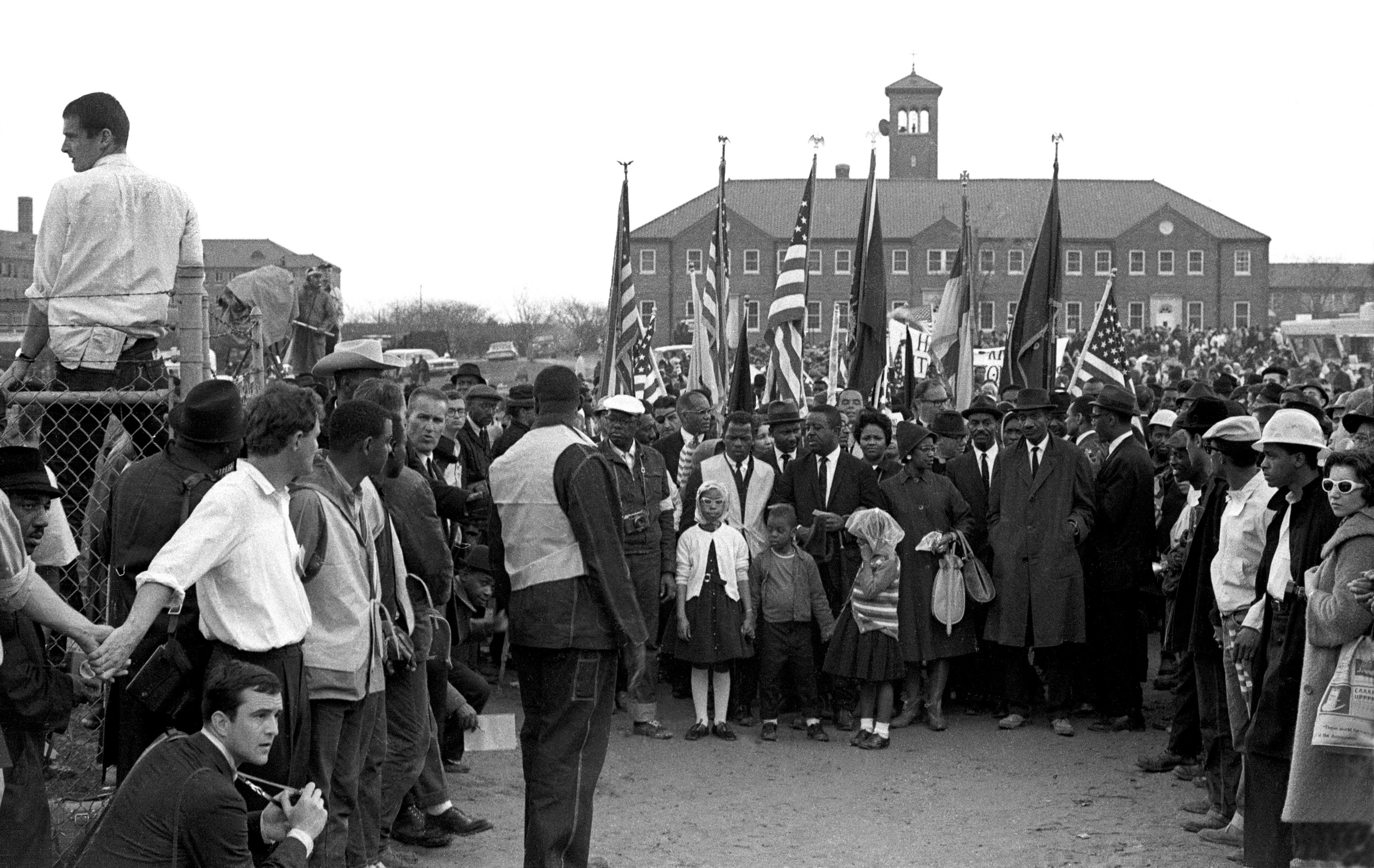 In this black and white image from 1965, John Lewis leads 25,000 marchers in front of City of St. Jude Church in Selma, Ala, who prepare to march to the capitol in Montgomery, Ala.