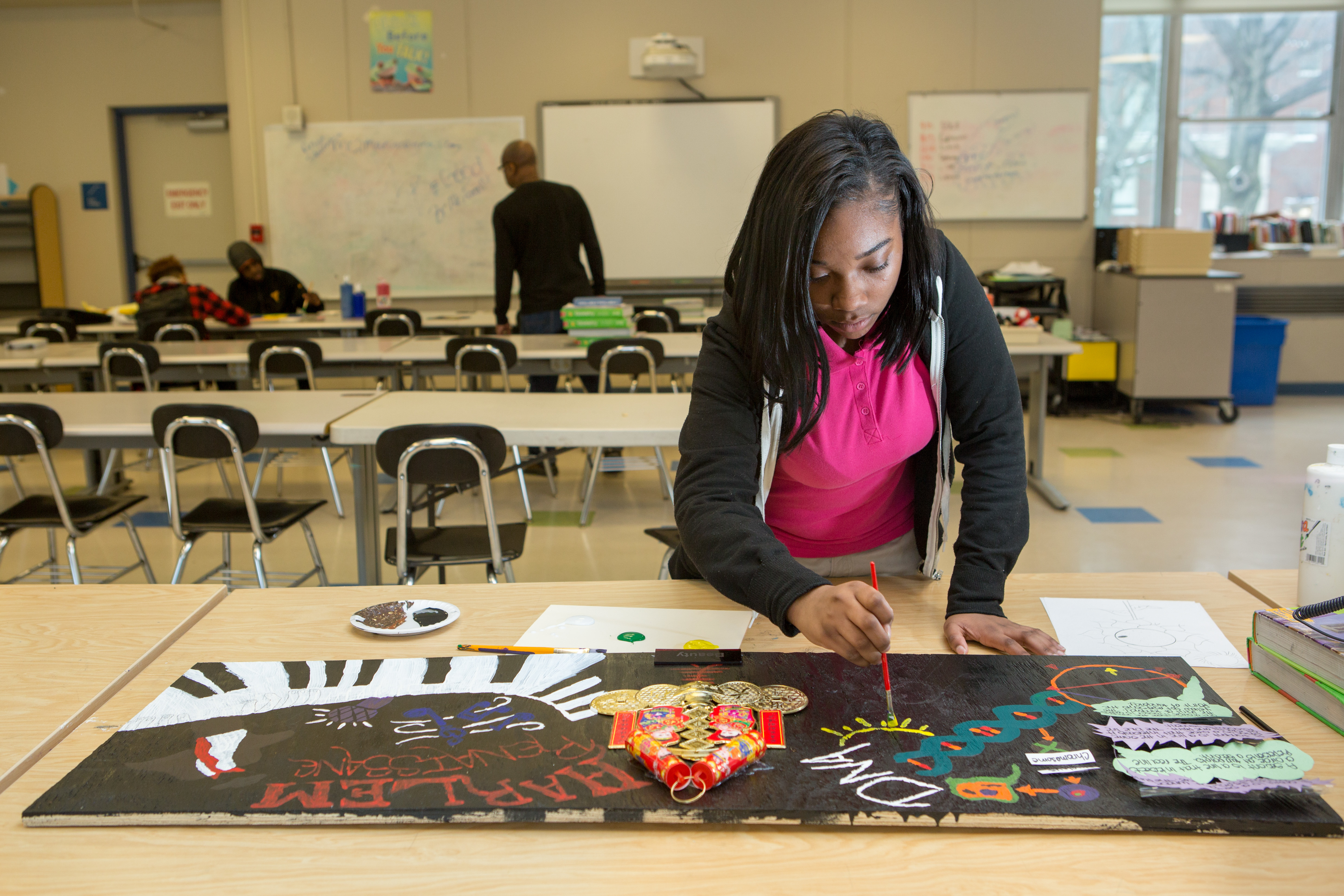 A girl wearing a black hoodie and a pink polo shirt works on an art project while other students speak with a teacher on the other side of the classroom.