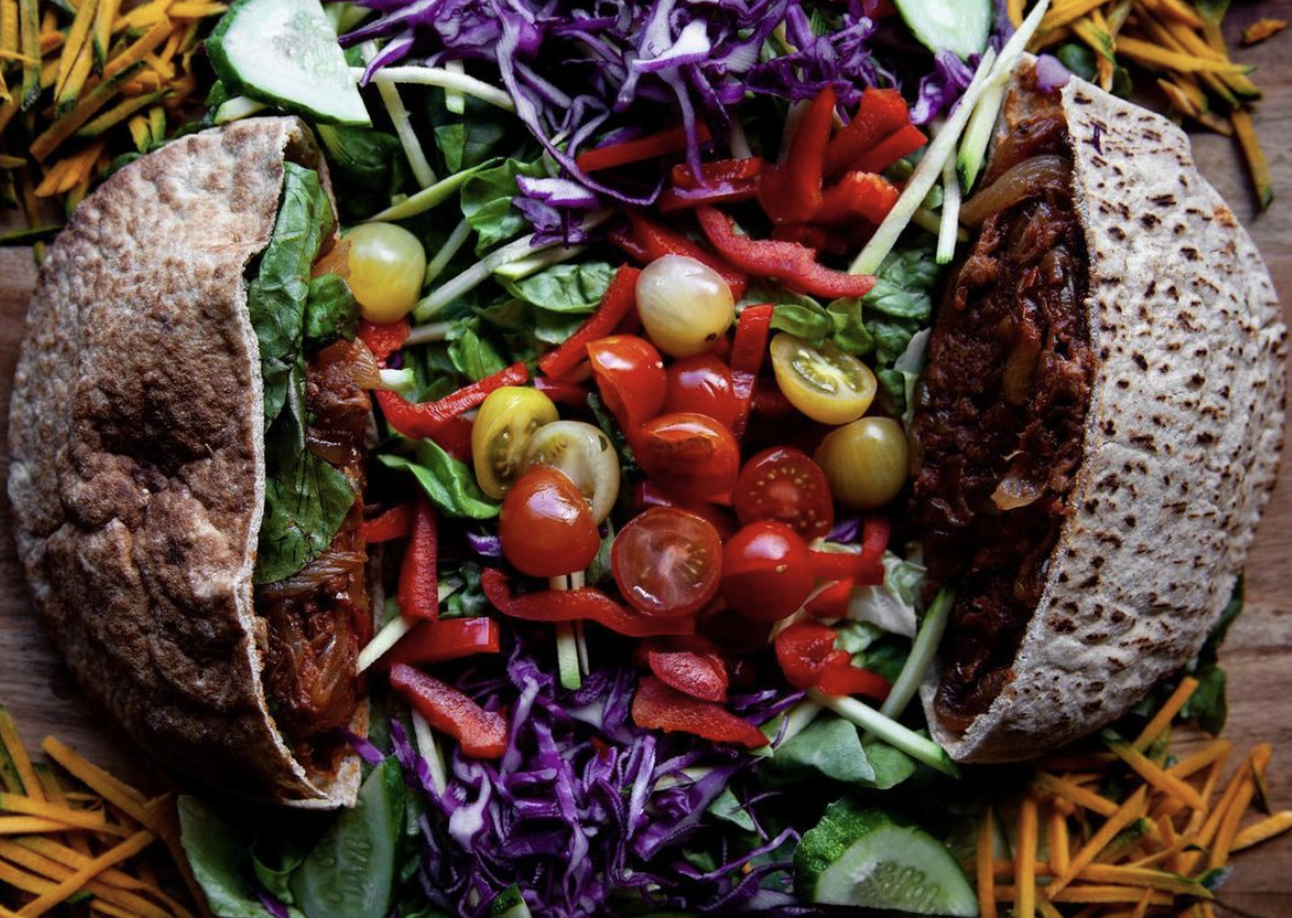 a pita split in half stuffed with yellow and red tomatoes, purple cabage, and a chickpea burger
