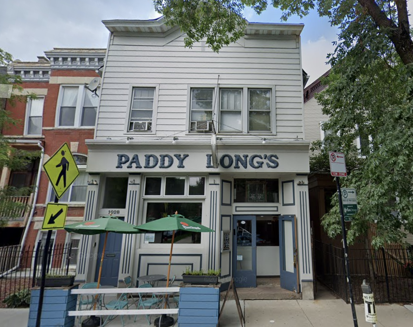 """A white storefront restaurant with blue letters over the door that read """"Paddy Long's"""""""