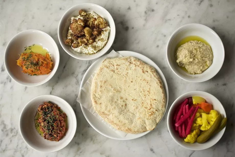 A picture of hummus, pita, pickles, and various other spreads in small bowls at Shalom Y'all