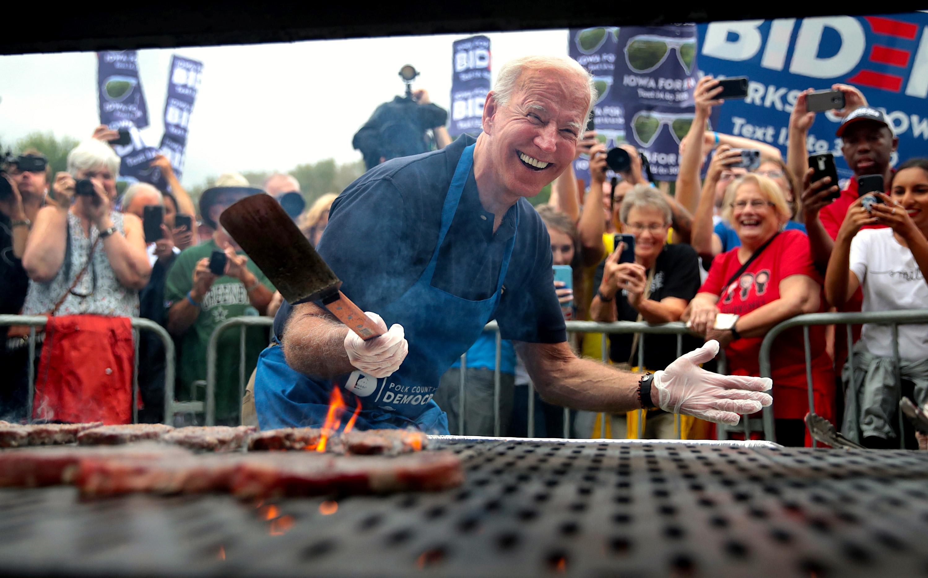 Joe Biden grills burgers on a grill at a campaign event.