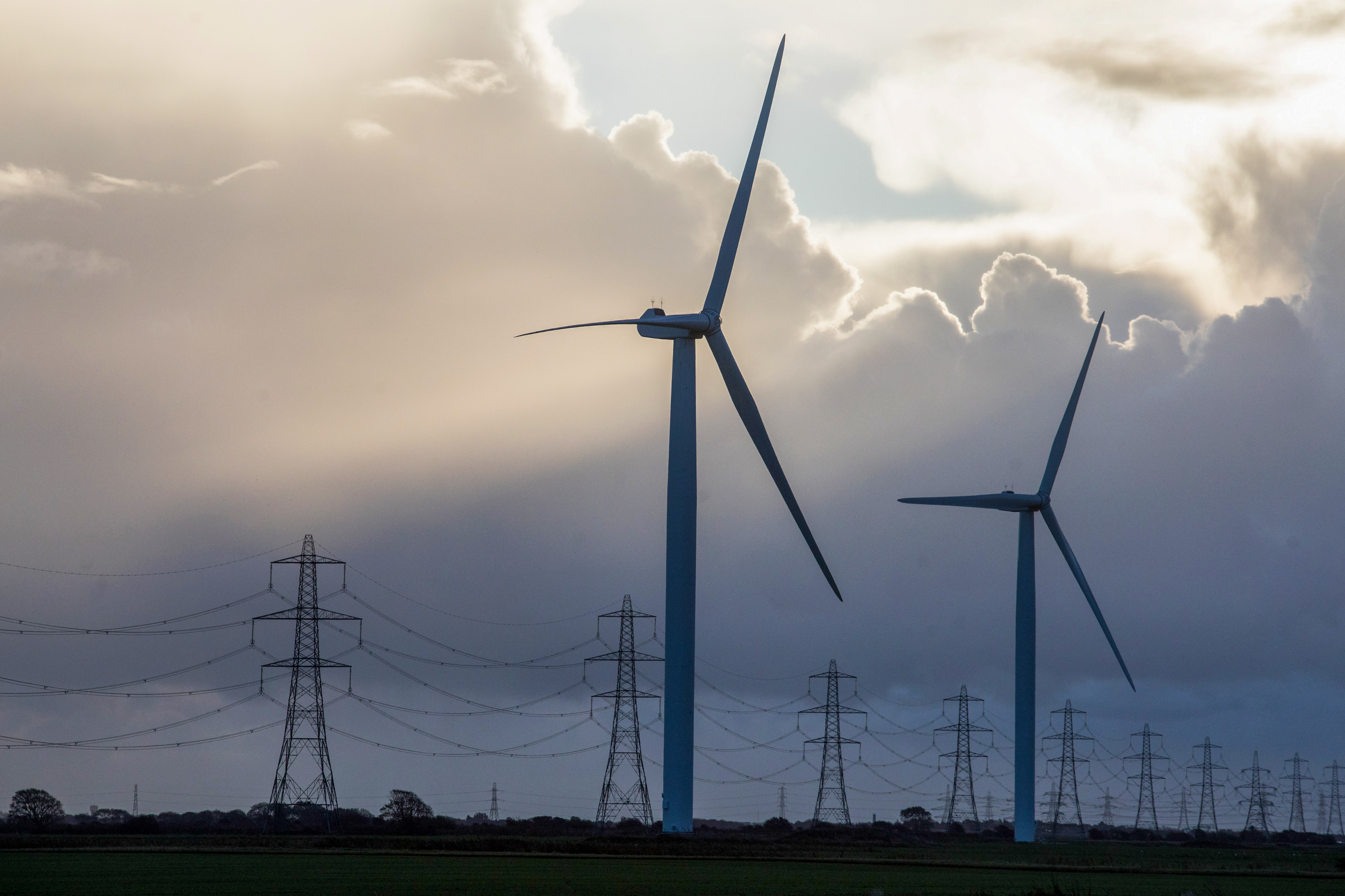 Onshore wind turbines and electricity transmission pylons at the Little Cheyne Court Wind Farm near Camber, U.K., on Monday, Oct. 26, 2020.