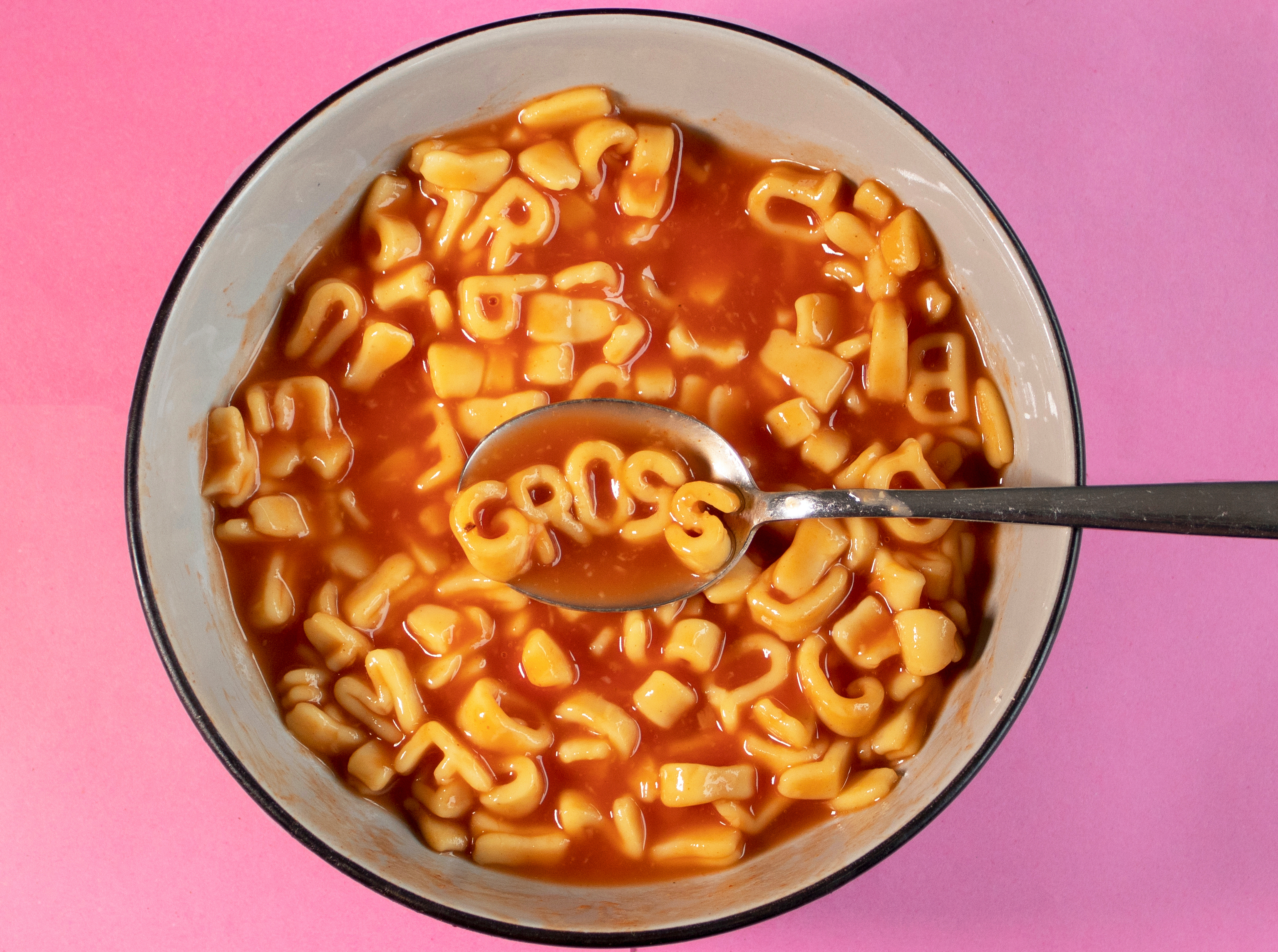"""The word """"gross"""" floats on a spoon in a bowl of alphabet Spaghetti-Os on a hot pink background."""