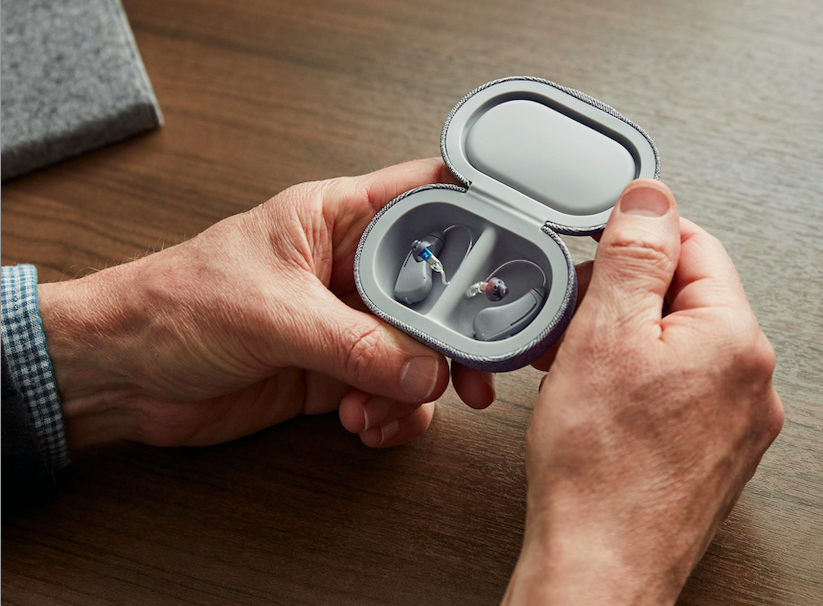 A pair of hands holding a small case with Bose hearing aids inside.