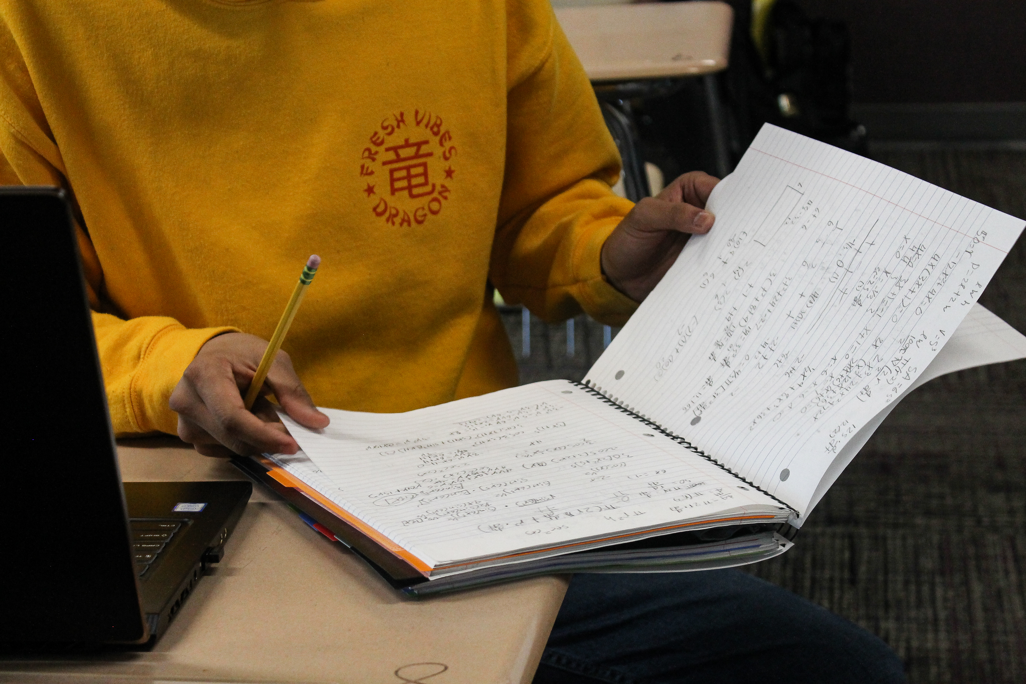A student in a yellow sweatshirt opens a notebook at their desk.
