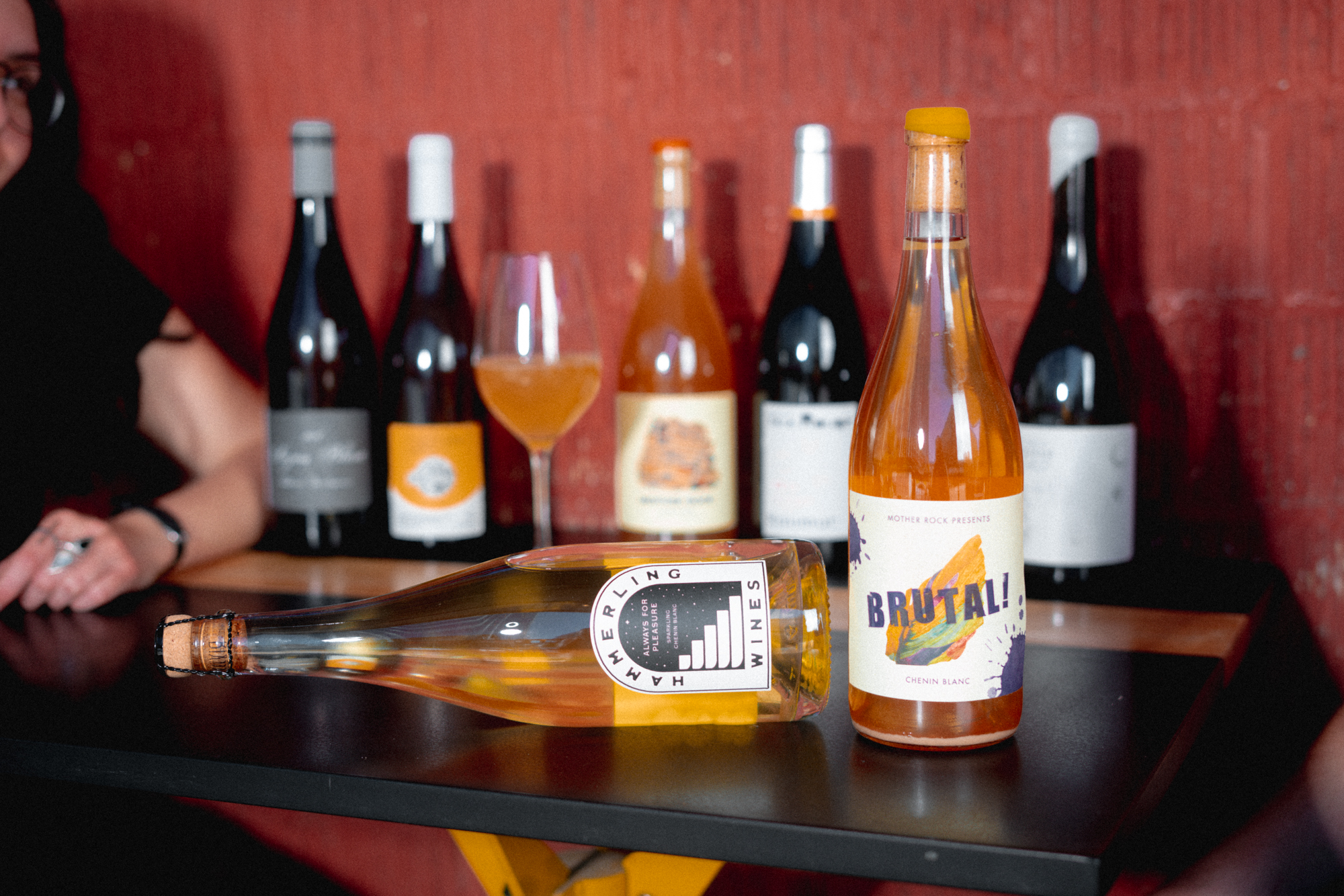Several bottles of wine including two in the foreground, one horizontal and the other with a label that says BRUTAL, on a wooden table against a red wall.