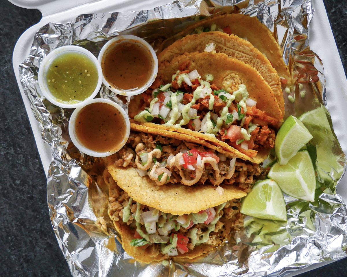 A photo of an assortment of vegan tacos from Mis Tacones accompanied by lime and salsa in a takeout box