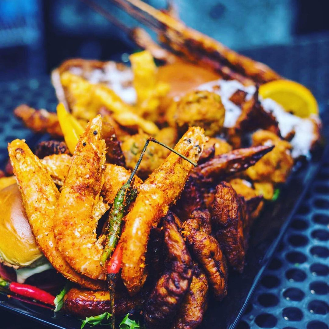 Fried seafood and sides are loaded onto a black tray