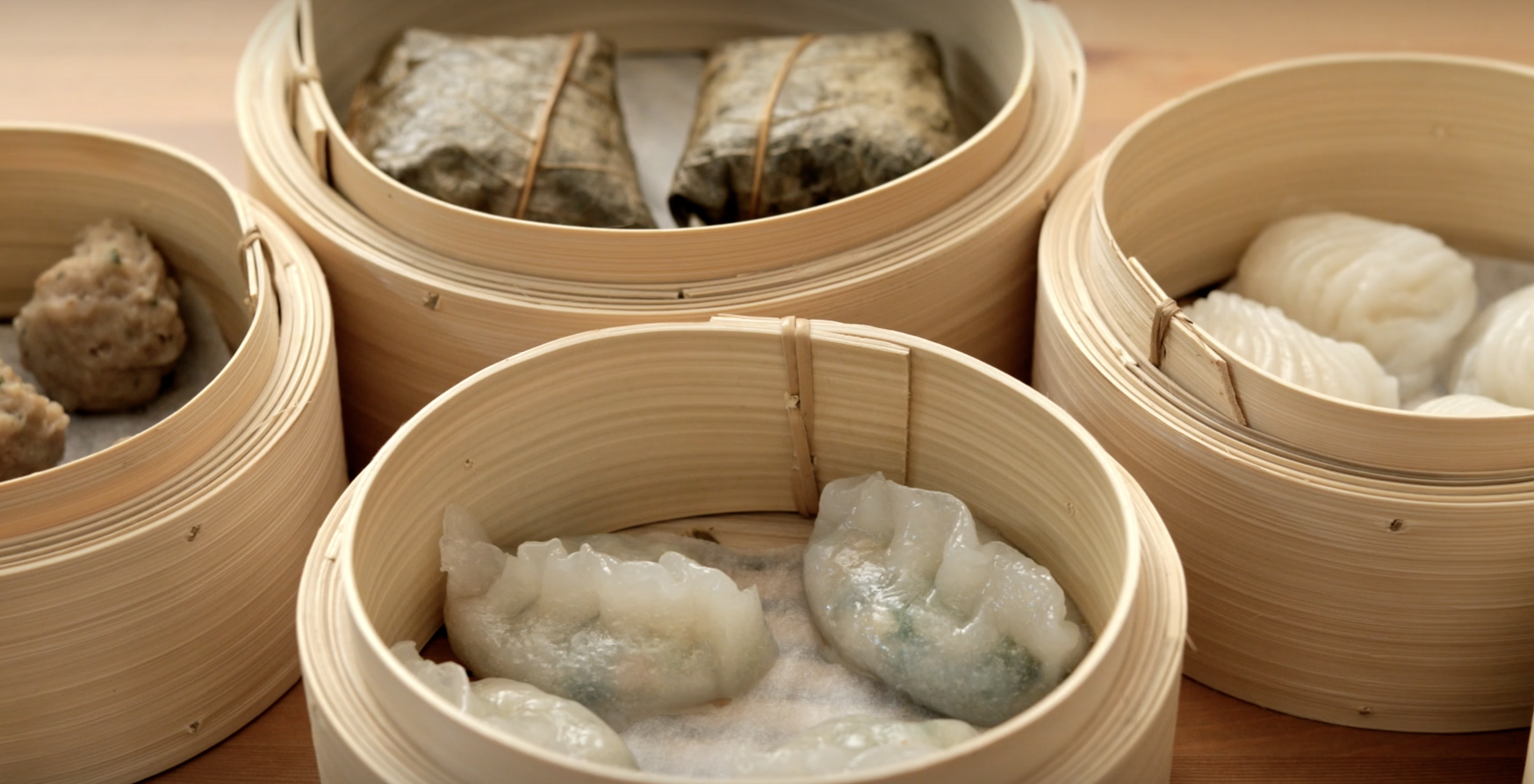 A still shot of a video showing moving steam trays of dim sum.