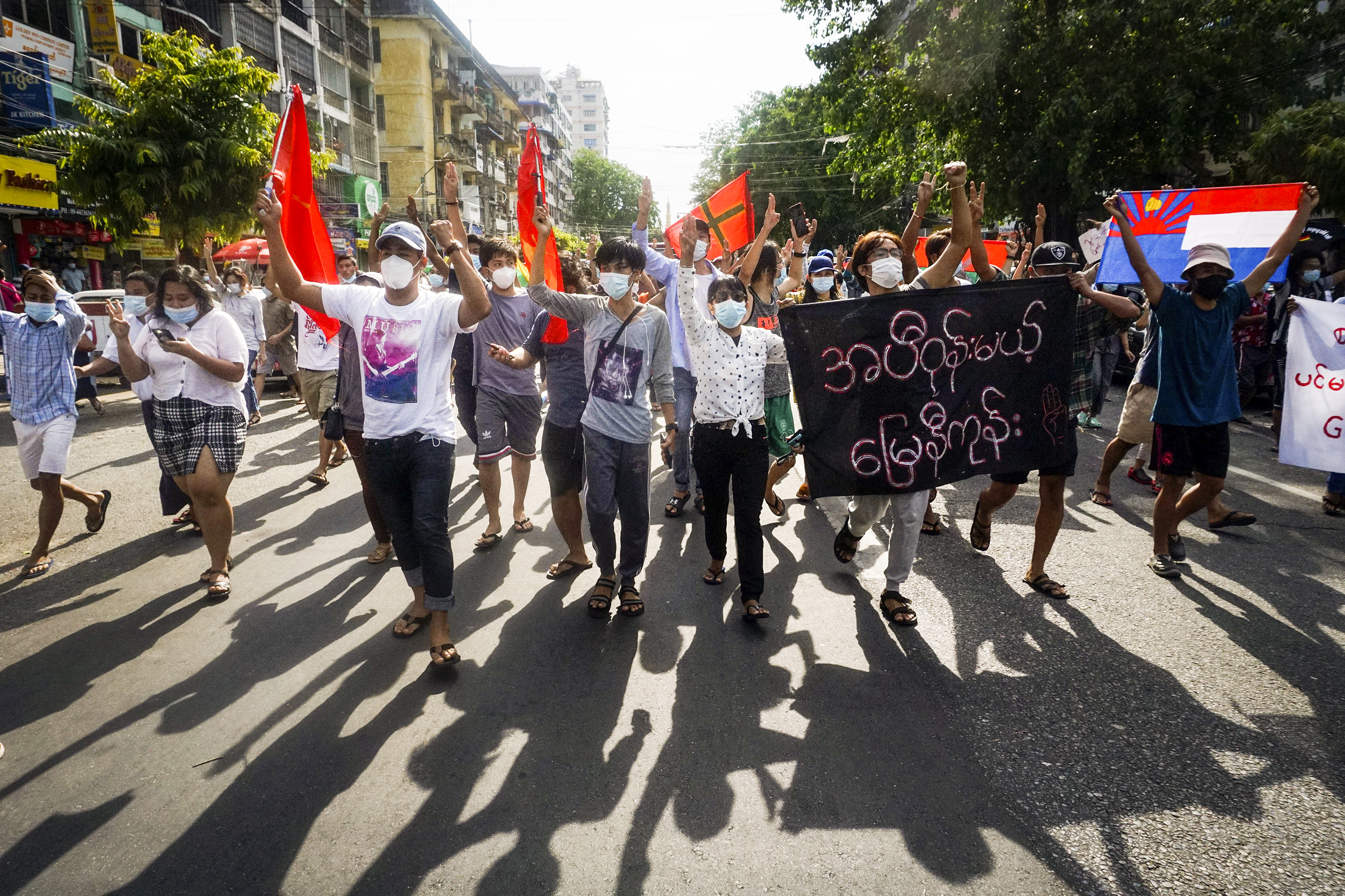 Masked protestors marching and waving flags in downtown Yangon, Myanmar, on May 6.