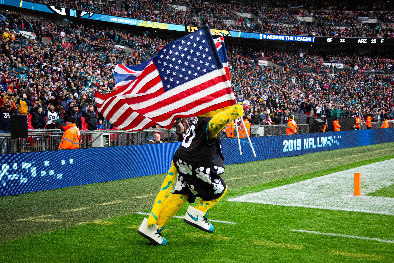 2019年11月3日,在英国伦敦温布利体育场,休斯顿德克萨斯人队和杰克逊维尔美洲虎队的NFL比赛开始前,杰克逊维尔美洲虎队的吉祥物杰克森带着国旗跑出赛场。