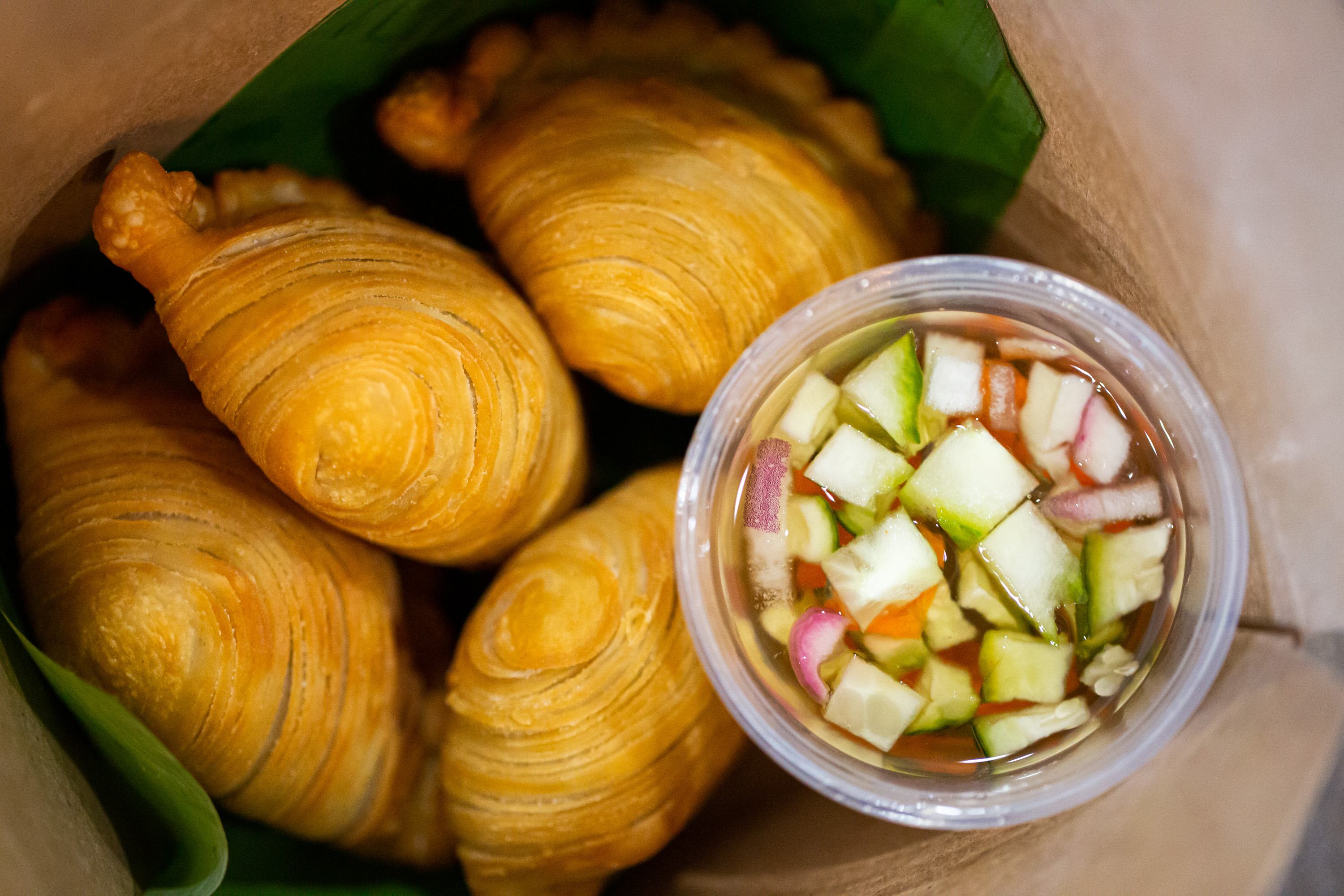 Curry Puff- Puffed pastries filled with minced chicken, sweet potatoes, onions, and curry powder w/ a side of cucumber salad in sweet vinaigrette from TydeTate Kitchen