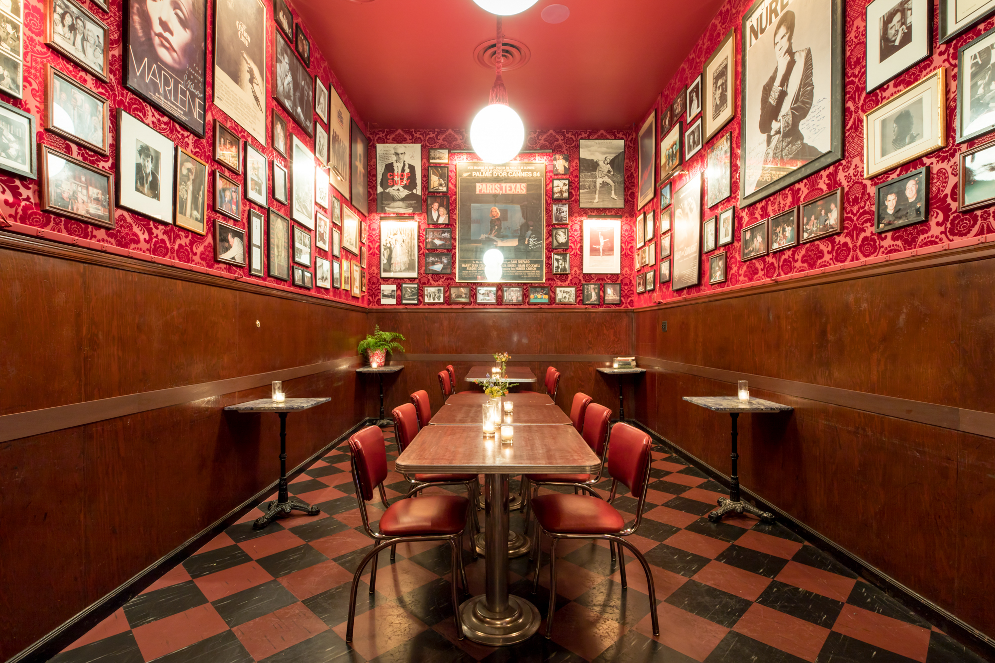 The interior of Tosca Cafe with red-and-black floors and art hanging on the walls above a wooden table