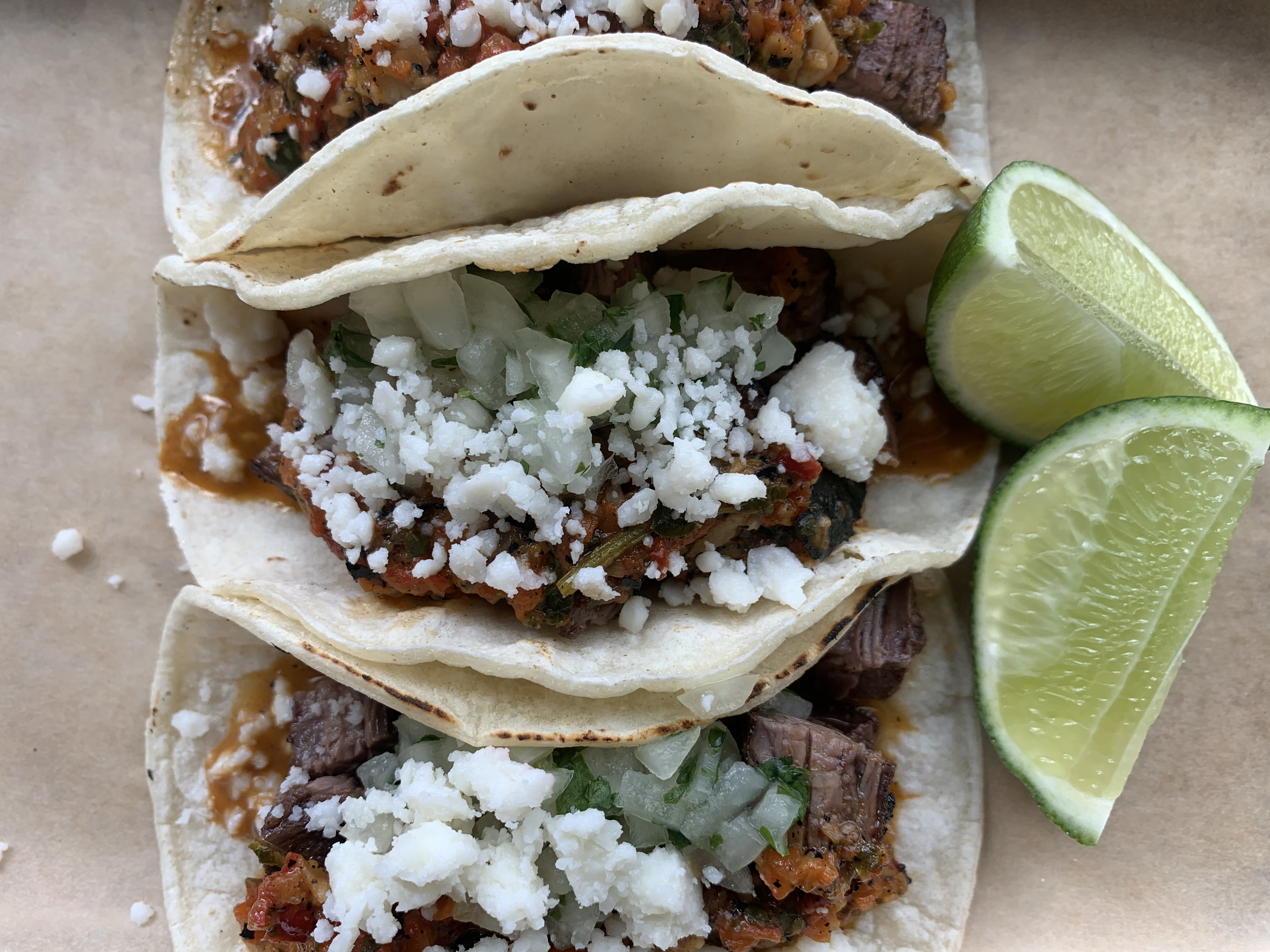 Three tacos, sprinkled with crumbles of cotija cheese, sit on a plate, adjacent to slices of lime