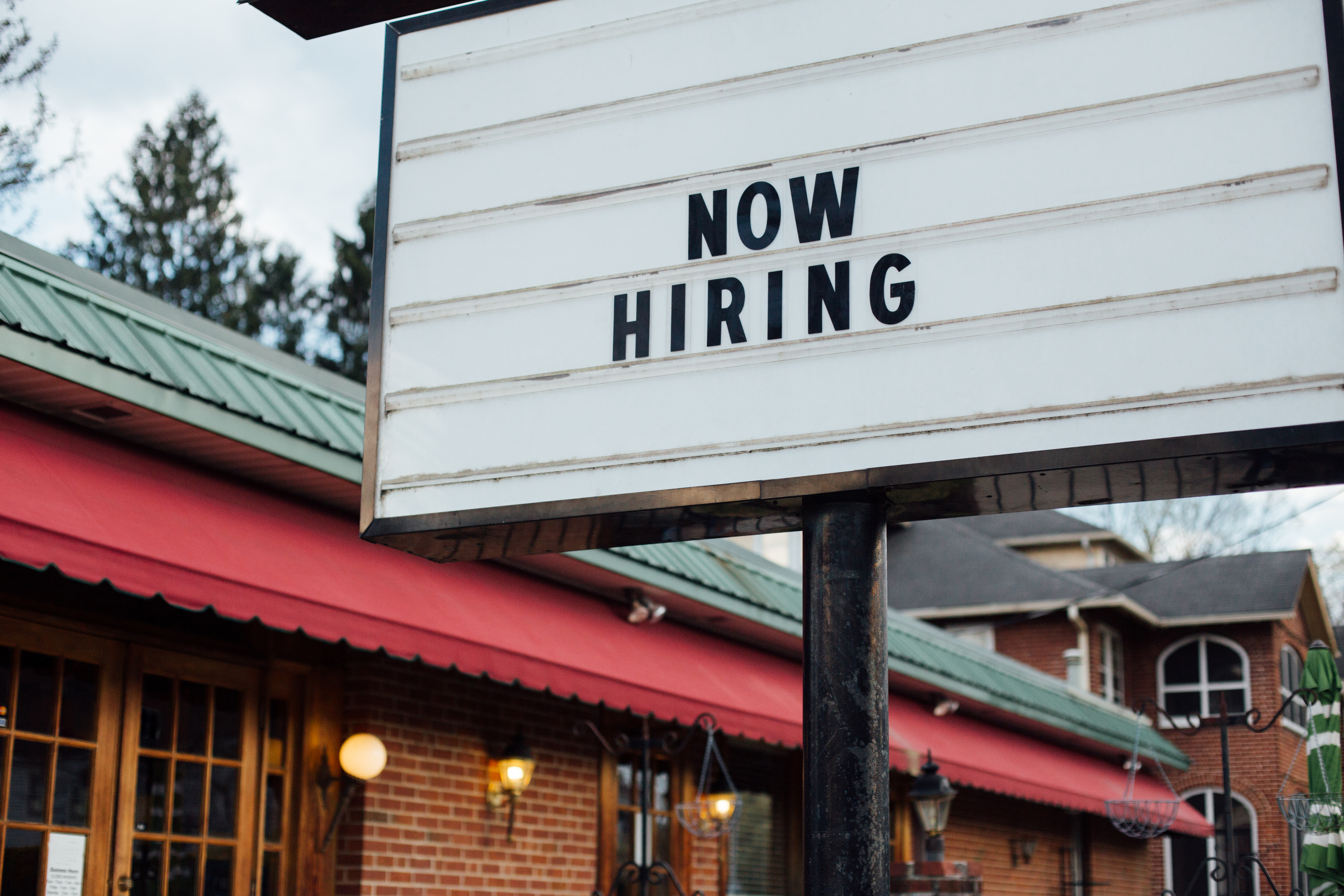 """A sign outside a brick restaurant reads """"NOW HIRING."""""""