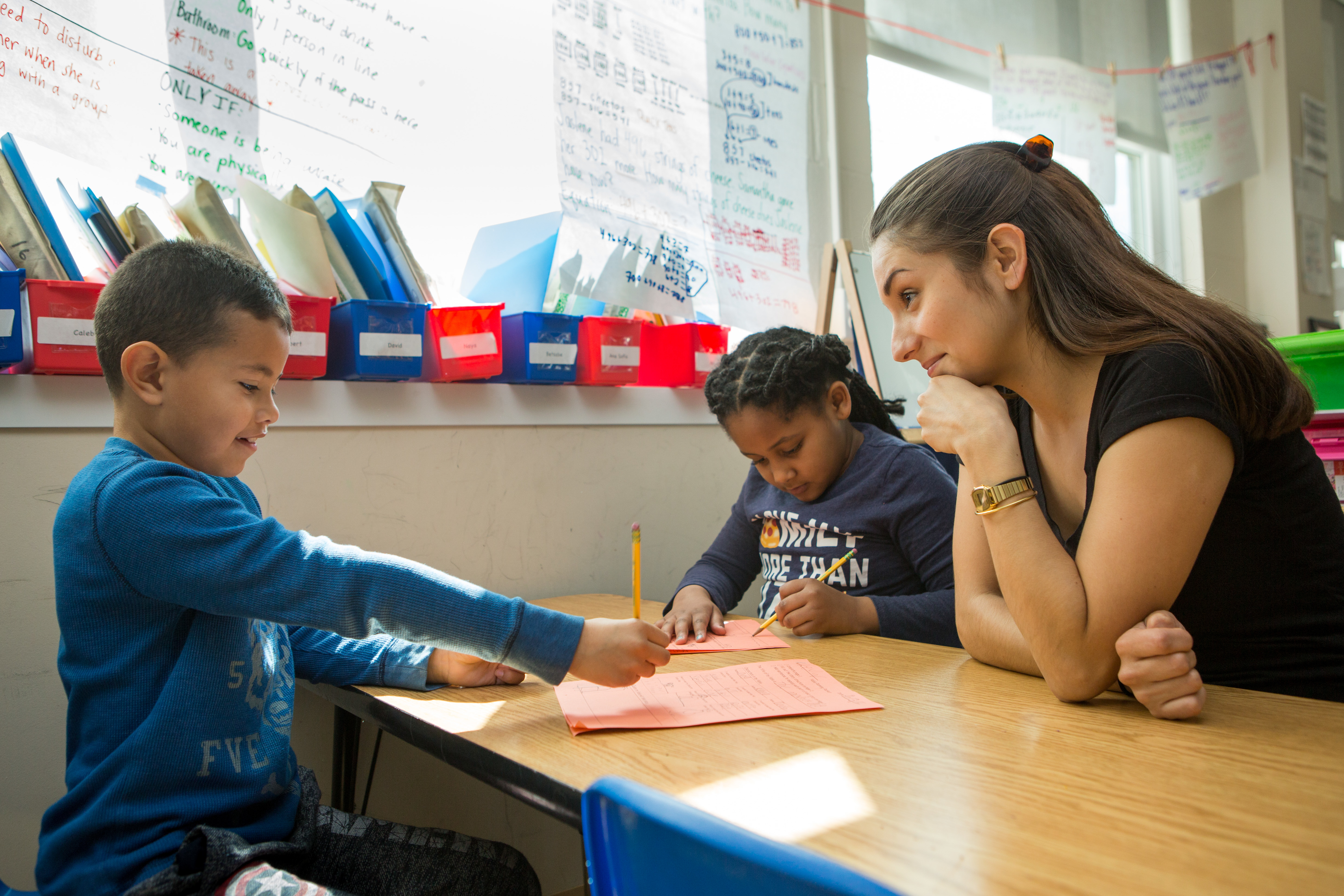 A smiling teacher sits at a table in a school classroom, looking on as a young boy and girl work on writing.